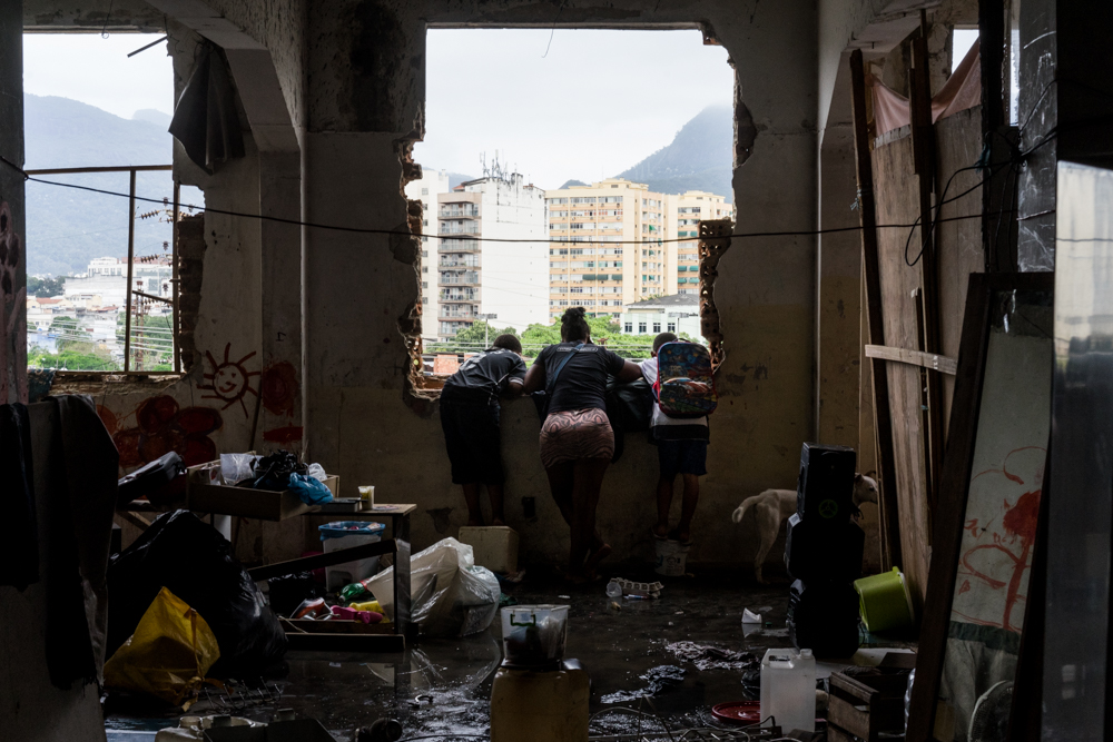 Luiza do Santos and two of her kids look down at police as an order is issued to vacate the old Ministry of the Economy building by noon. (Photo: C.H. Gardiner)
