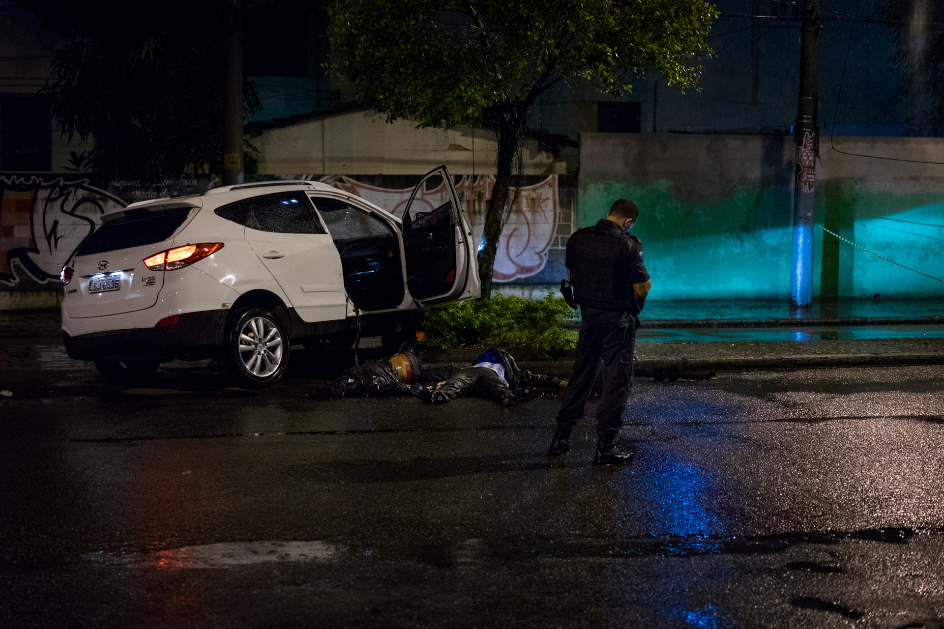 A Brazilian police officer stands watch over two alleged gang members shot by police after they ran a checkpoint 4, April 2018.