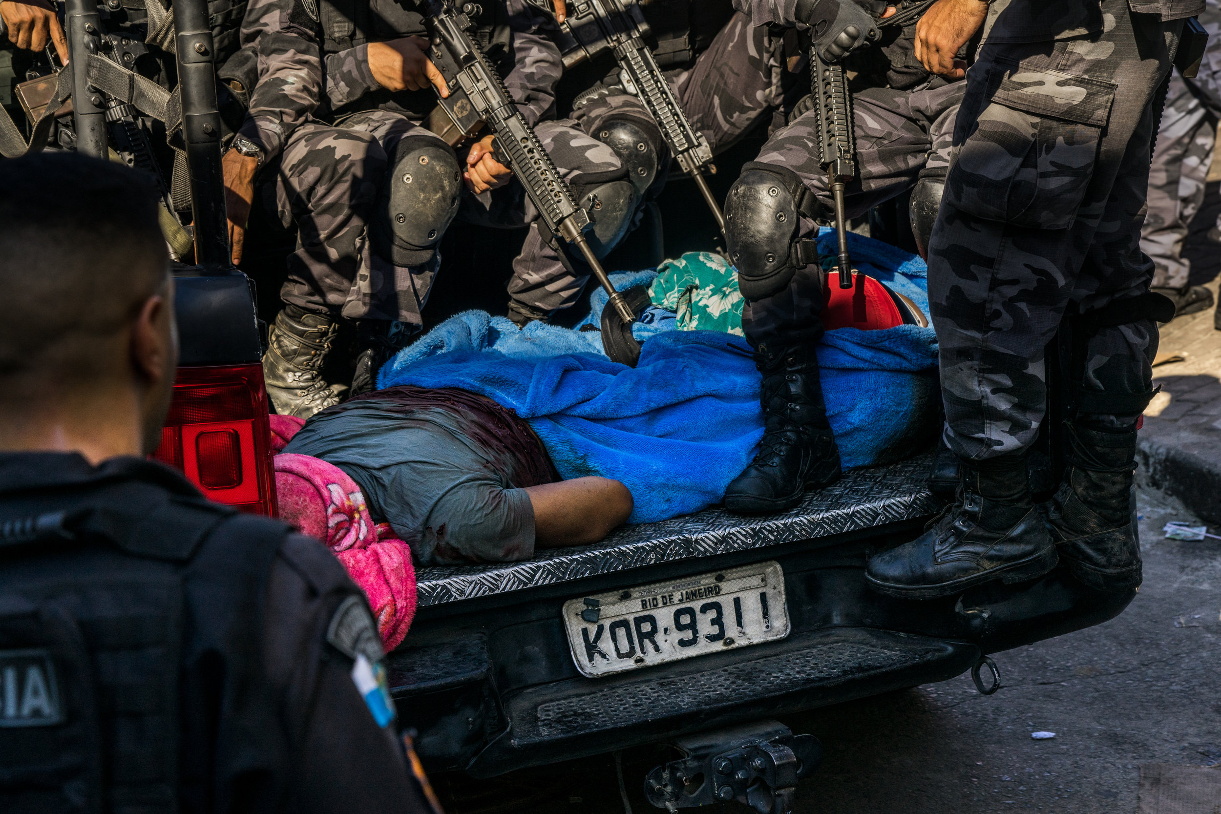 Soldiers remove the bodies of alleged drug dealers following an early morning operation in Rocinha favela on March 24, 2018. Locals say that at least two of the eight killed during the operations were innocent. (C.H. Gardiner)