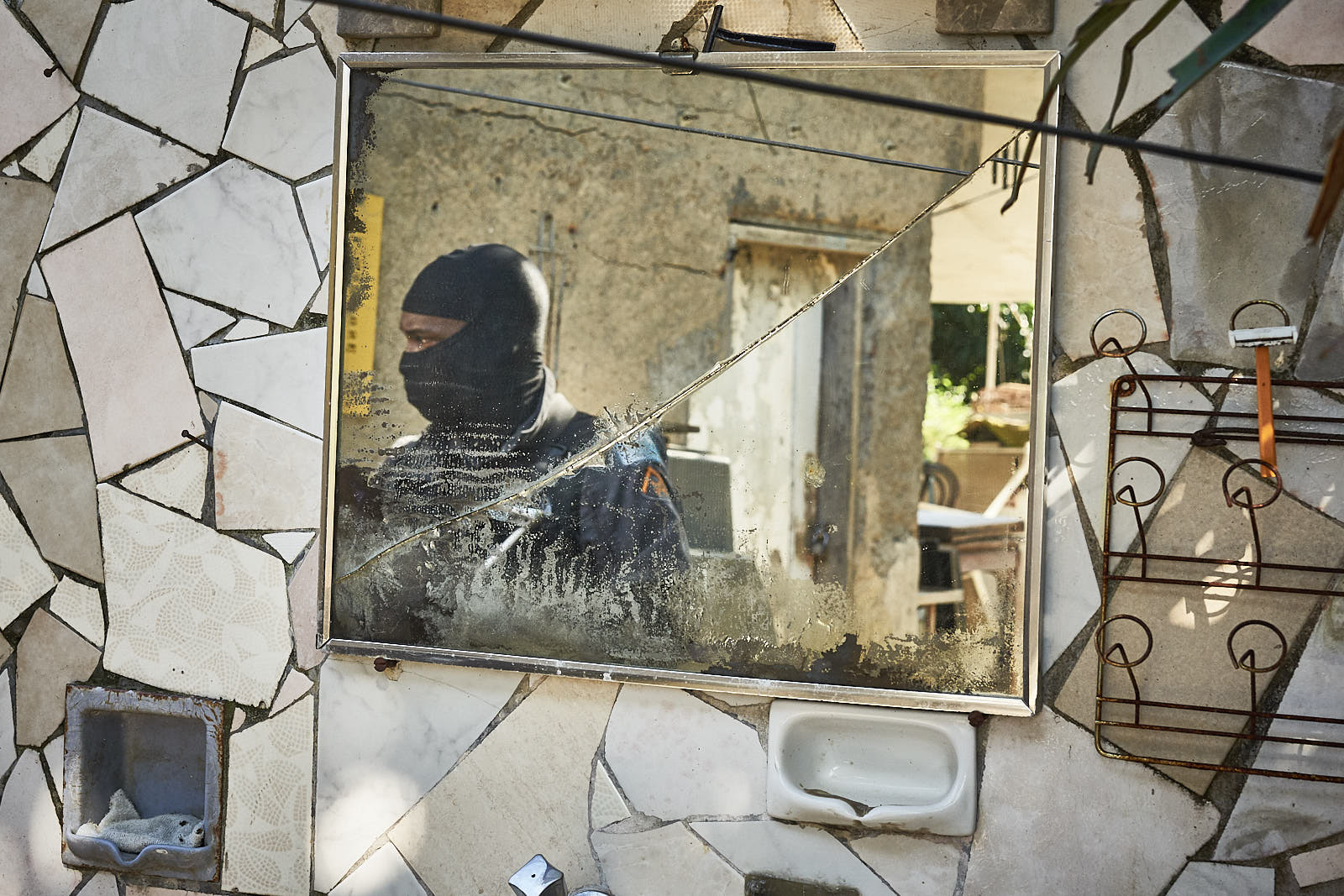 A broken mirror reflects a masked soldier from Rio's Military police during an operation in Morro da Babilônia, a favela located next to Copacabana beach. Many police choose to work masked to minimize the threat of being recognized when off duty. (Photo C.H. Gardiner)