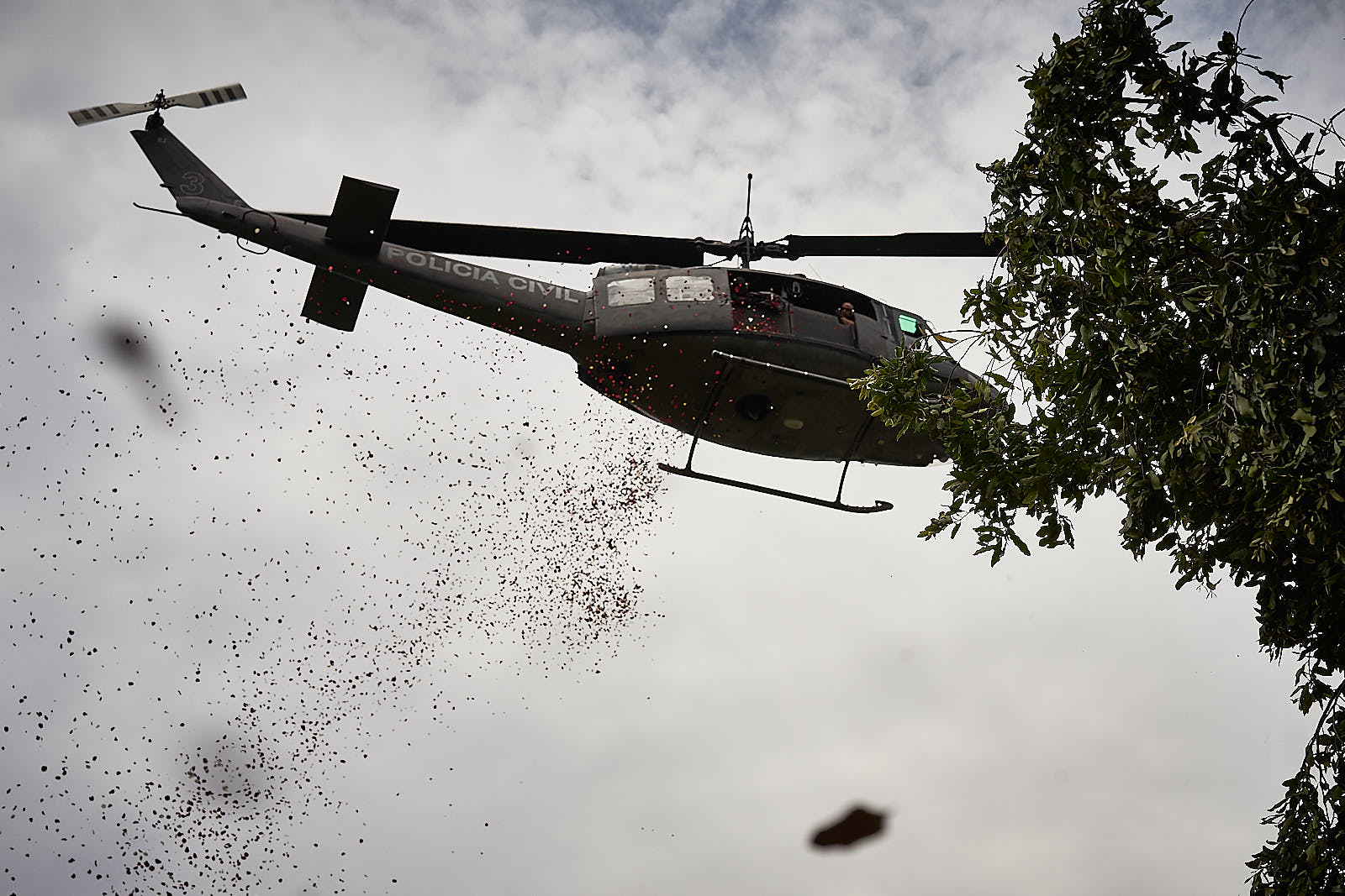 A helicopter from the Civil Police drops flowers on the funeral of Delegado Fabio Monteiro, a police officer executed by criminals. Residents of Jacarezinho say that police used the helicopter to shoot indiscriminately into the community as retaliation. (Photo C.H. Gardiner)