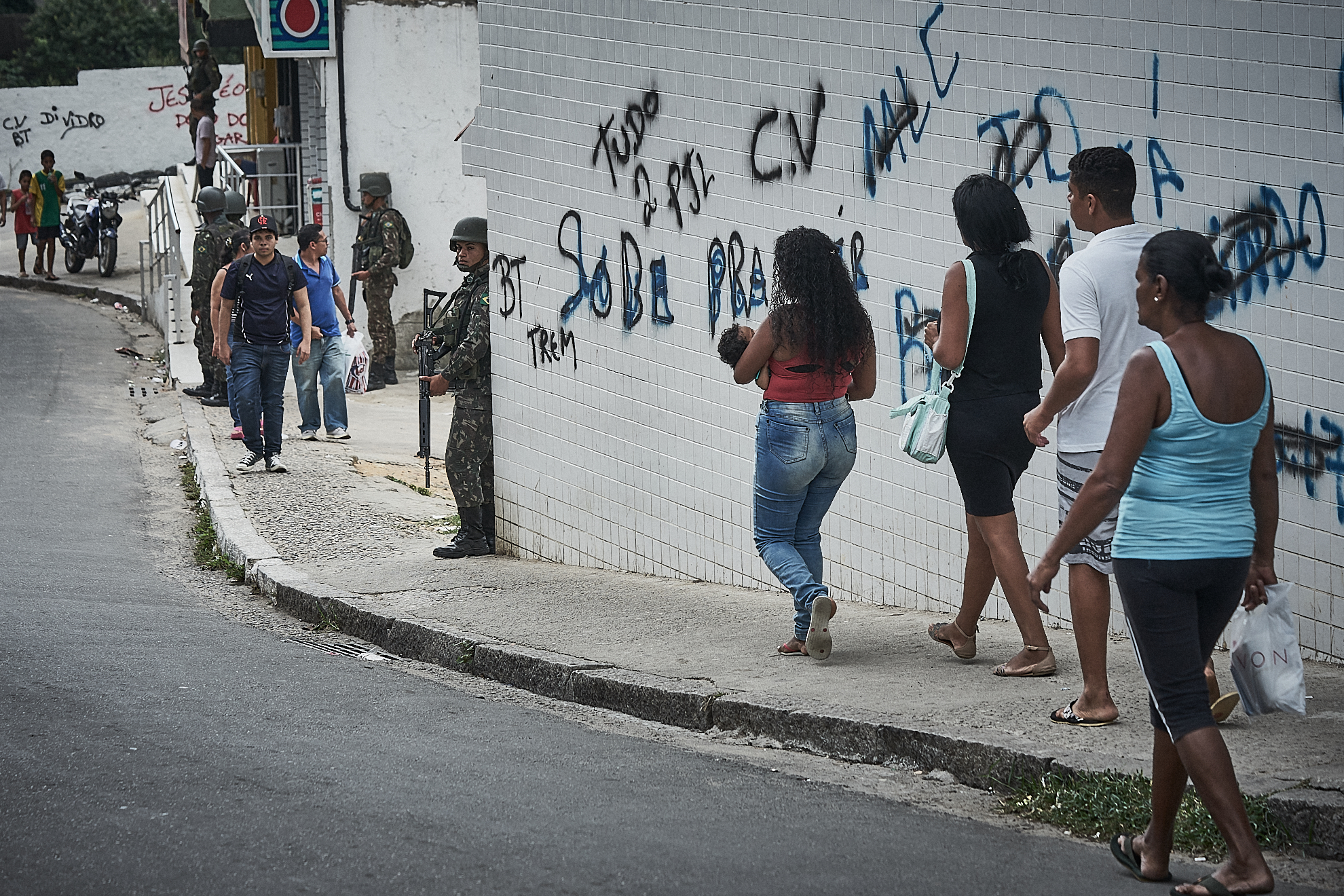 "Residents of Praca Seca walk the street during a military operation targeting organized crime in the area. The graffiti on the wall reflects the frequent changes in ""ownership"" between militias and the narco-gang Comando Vermelho.(Photo: C.H. Gardiner)"