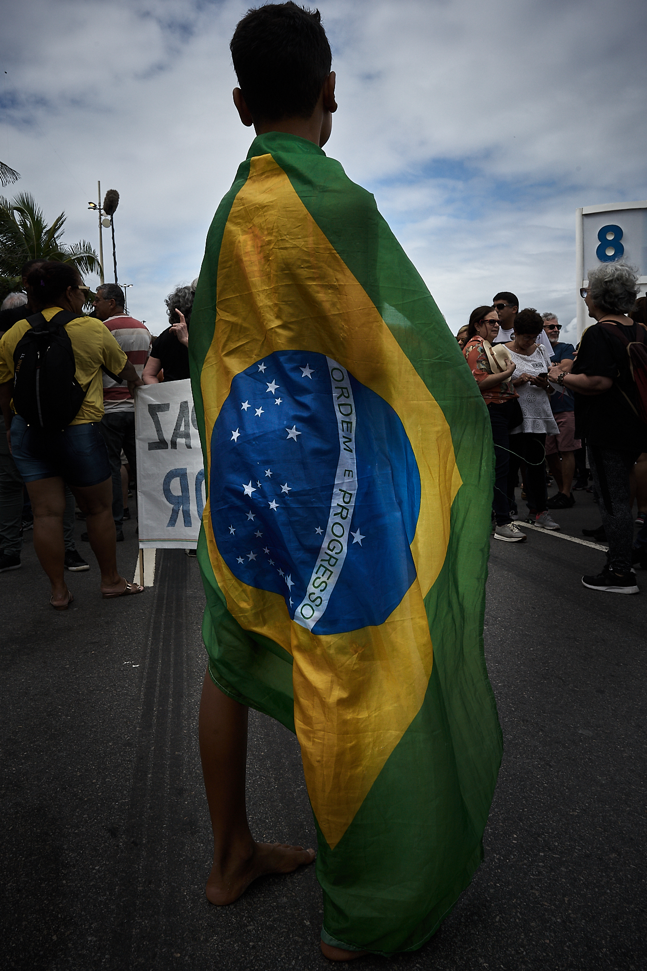 A boy stands draped in Brazil's flag at a protest against the increased violence in Rio's Favelas. (Photo: C.H. Gardiner)