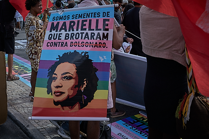 A protestor against police violence holds a sign with Marielle Franco's face (Photo: C.H. Gardiner)