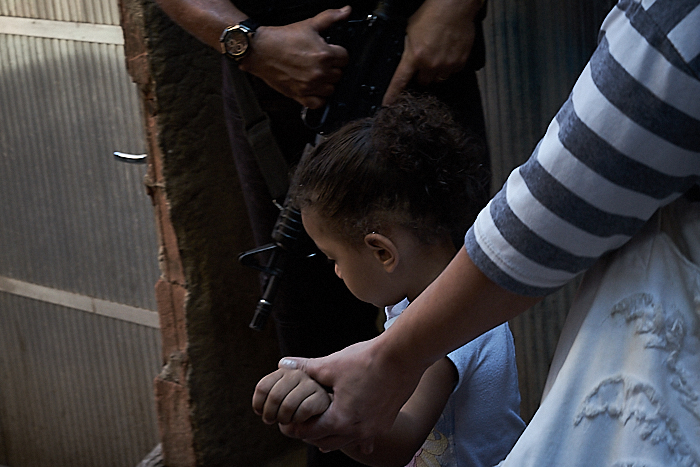 A woman walks with her child past police in Rio de Janeiro. (Photo: C.H. Gardiner)