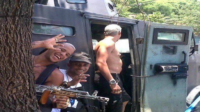 Armed traffickers pose next to an armored vehicle used by police. (Photo: Police Release)