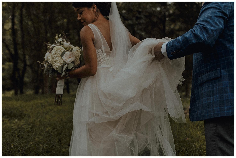 groom holding wedding dress