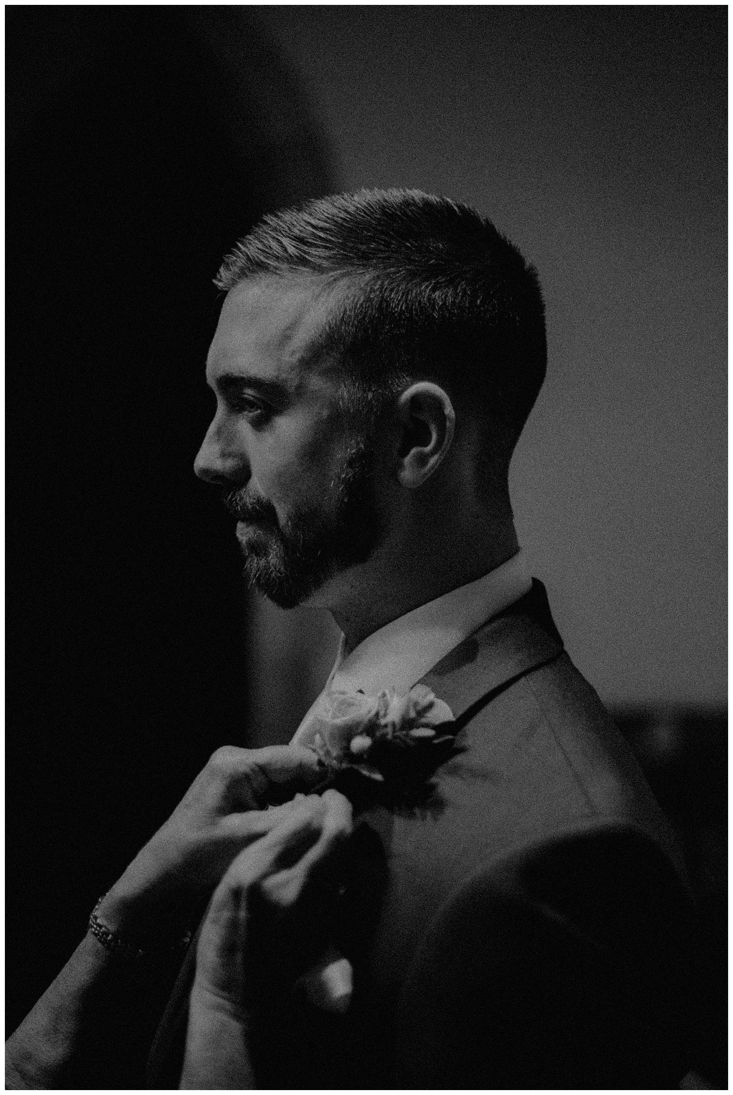groom putting on flower