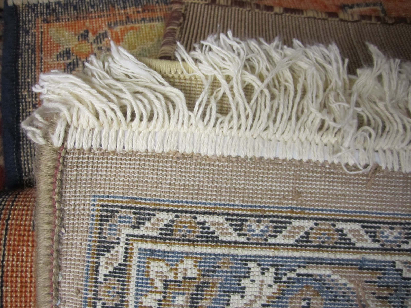 Machine made rug with sewn on fringe.