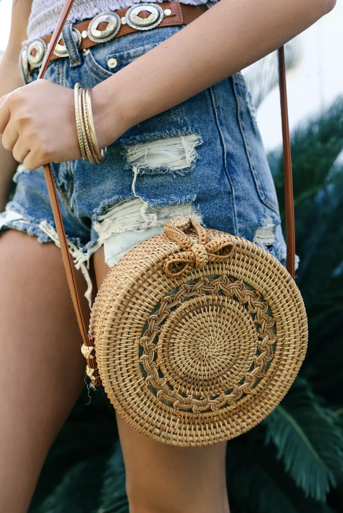 Stroll the sandy shores with the Port Costa Tan Round Woven Purse! Woven rattan shapes this unique, woven round tote with a cute cut-out design. Matching loop closure opens to a roomy interior, while the long genuine leather shoulder strap adds a touch of luxe.