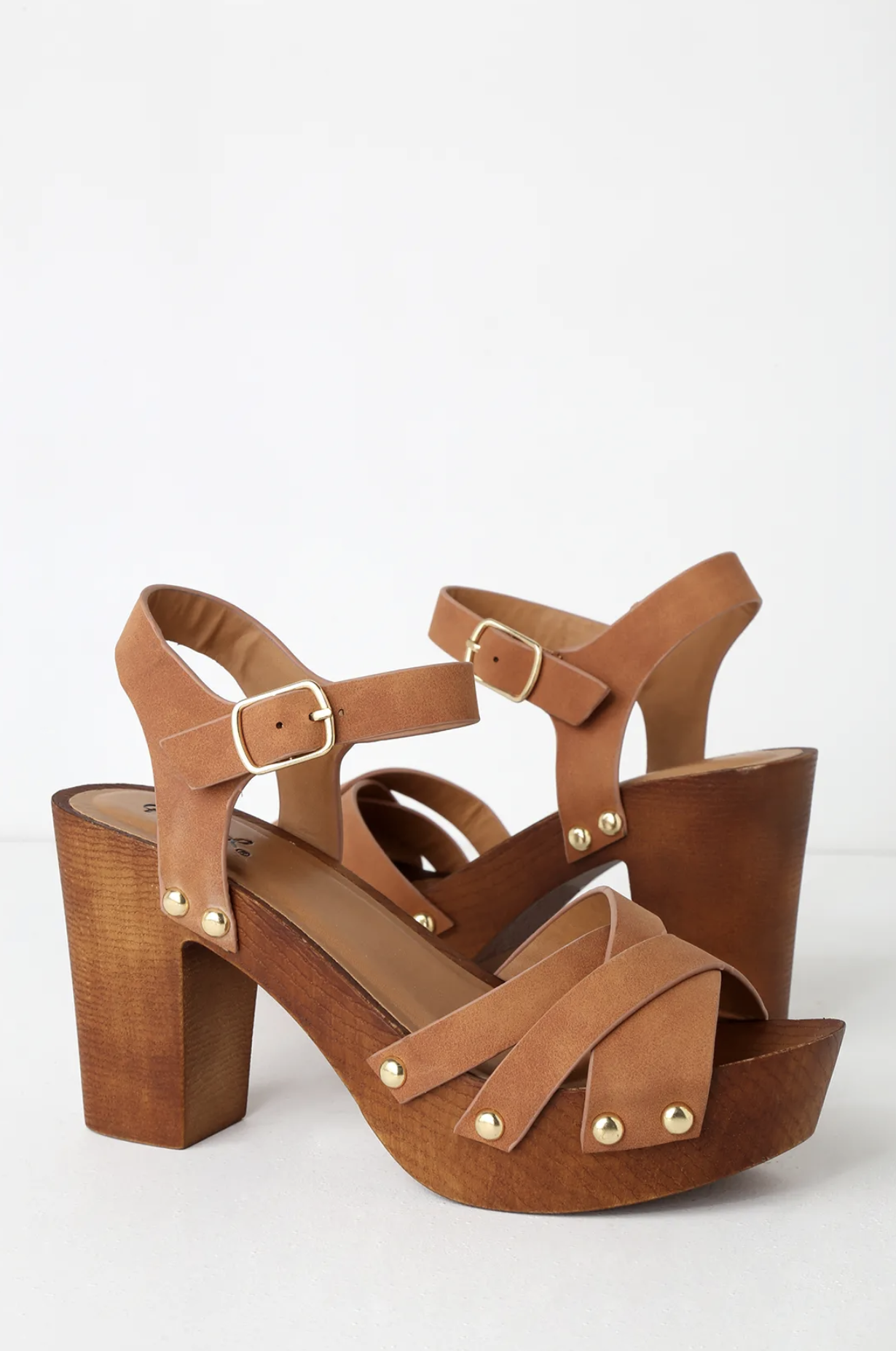 """Add a trendy touch to your look with the Talia Camel Distressed Nubuck Wooden Platform Heels! These on-trend heels start at a vegan nubuck peep-toe upper, shaped from crisscross straps, then carries into a matching quarter strap with shiny gold rivets and a gold buckle all atop a cute 1.5"""" wood-look toe platform."""