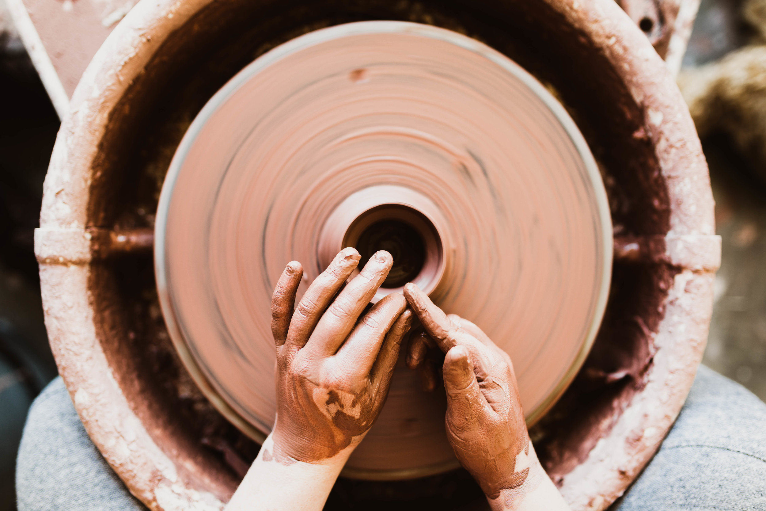 """A person's hands crafting pottery on a spinning wheel"" by  Jared Sluyter  on  Unsplash"