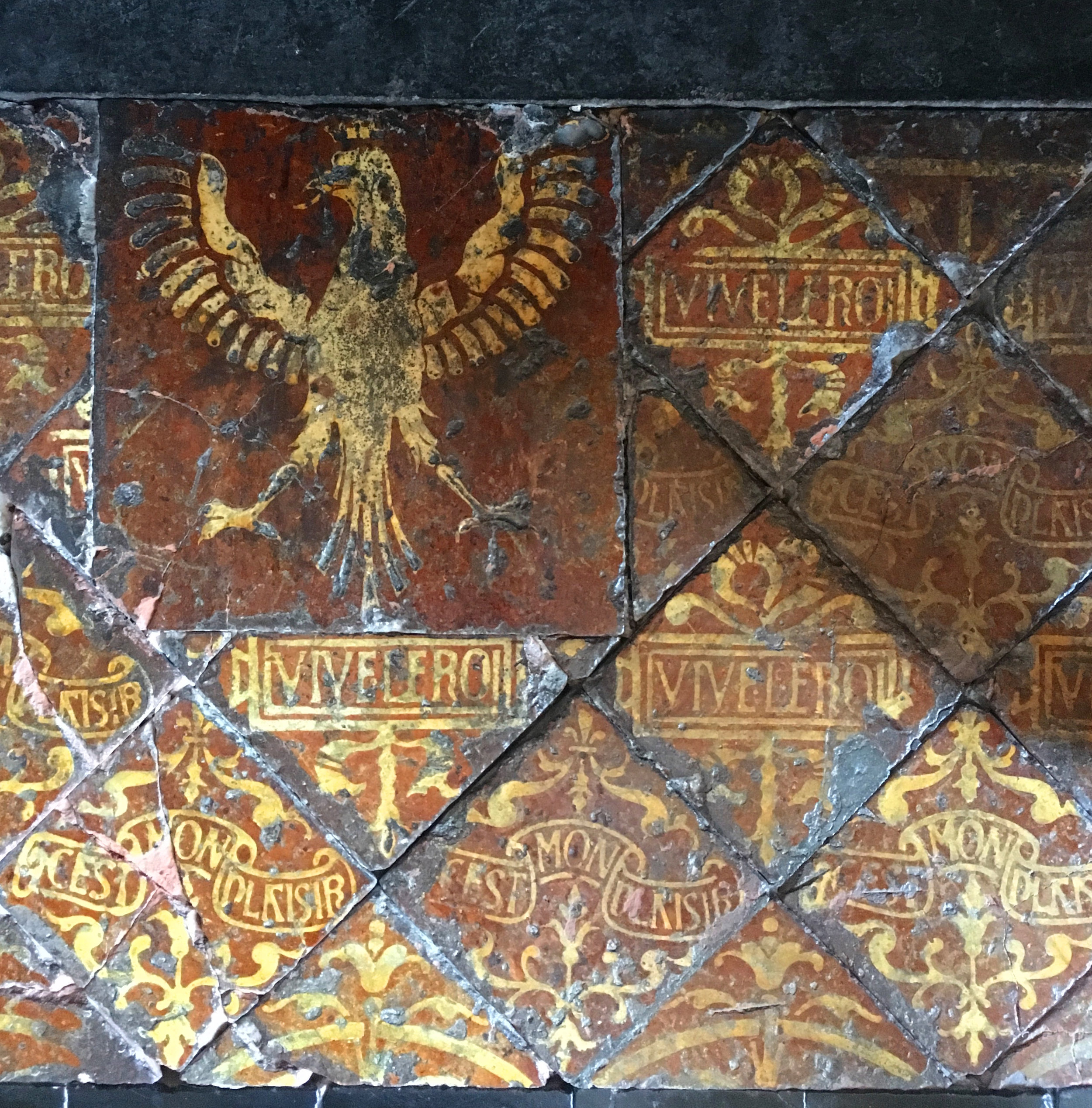 Early tiles that marry heraldry and mottos, Ancy le Franc Château (photograph J. Cook)