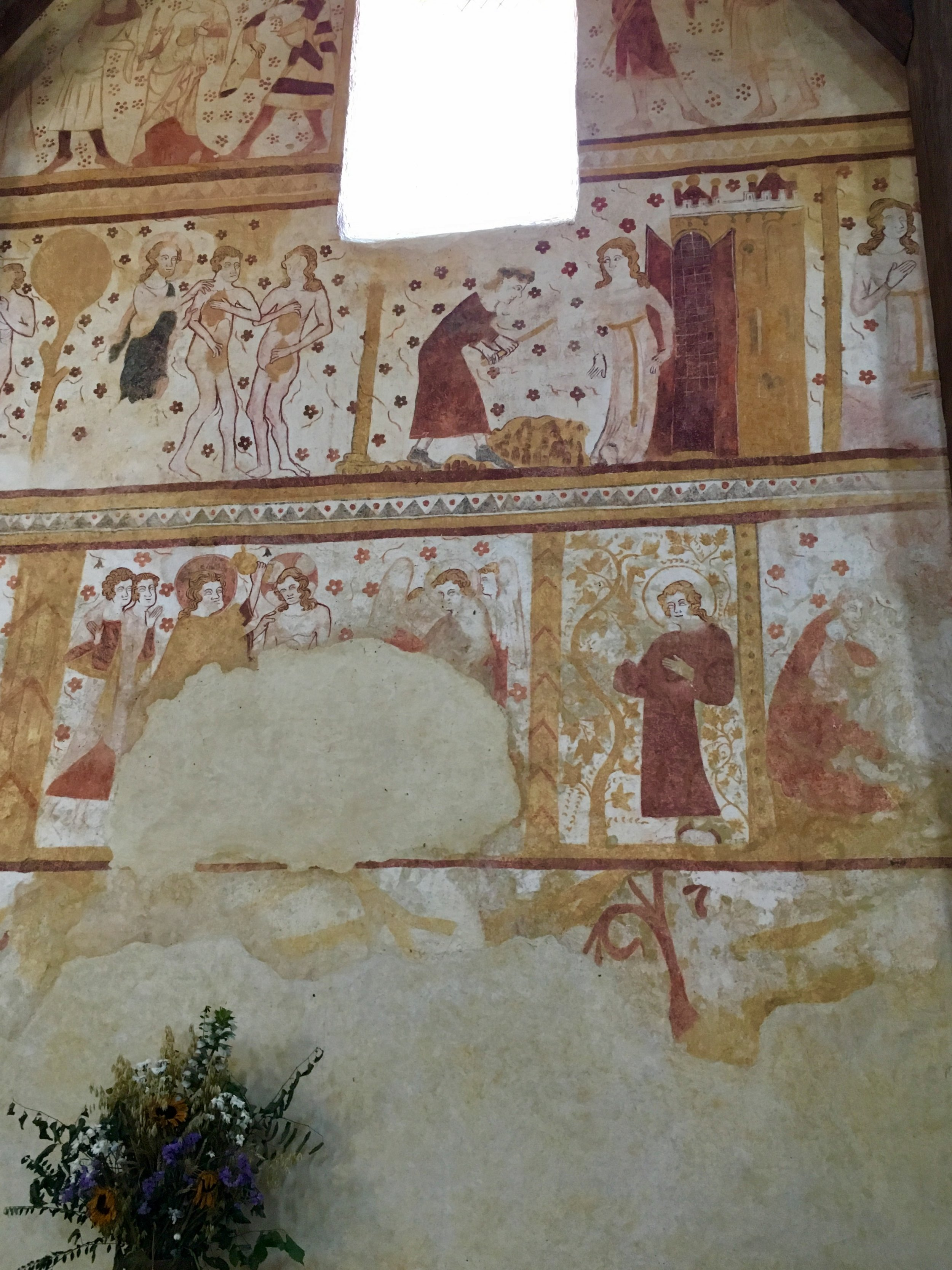 Eglise St. Pierre, south wall, 13th century ochre frescoes.  Above, Adam and Eve being ejected from Paradise and working hard; below, St. John preaching and Christ being baptised.(photograph J. Cook)