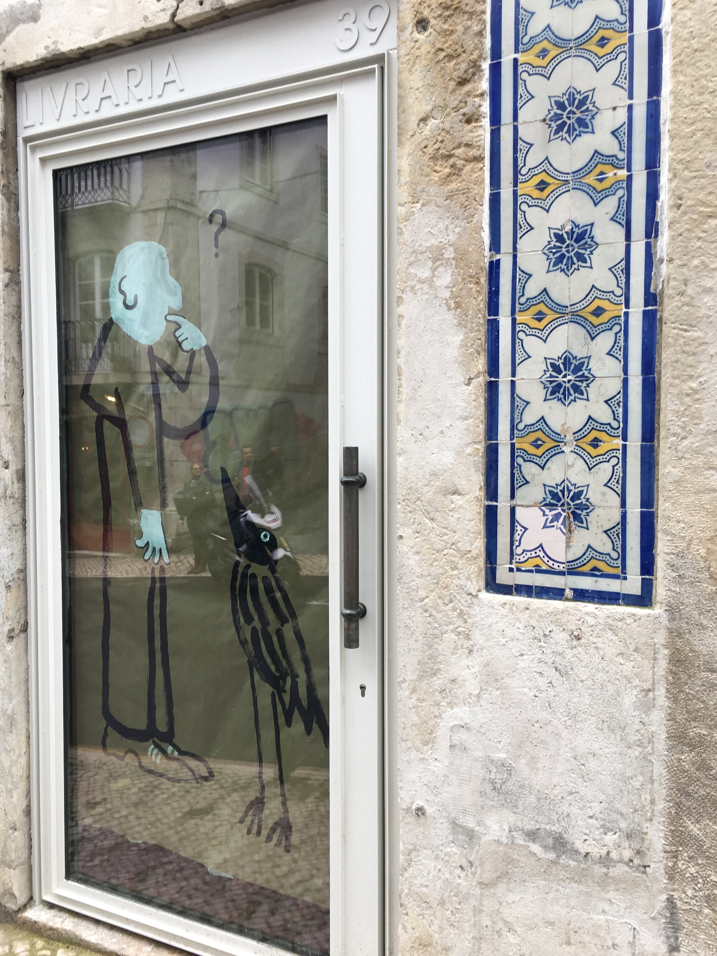A flourish of wall tiles on a deliciously humorous art gallery R, with its window obscured during an exhibition change. Rua da Esperança Lisboa. (photography J. Cook)