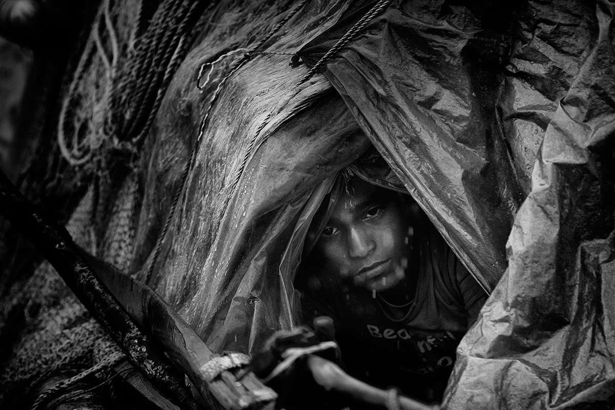 "A son of a hilsa fisherman huddles inside a boat away from the rain, waiting for his father to return. Pirates had kidnapped him and held him for nine days. Did he have a chance to escape? ""I was on a boat, where would I escape to? No, it is best to wait out these kidnappings."" They fed him once in two days, he said. On the appointed day, he was returned to his parents for 20,000 Taka (about $255) in ransom."