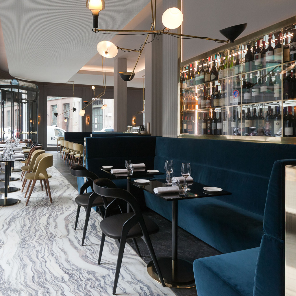 - Instead of going with the obvious choice of a marble table top here,the black table and dining chairs at Milan hotspot T'a Milano bring a masculine edge to the super glam brass chandelier and teal velvet booth.Image via Habitually Chic