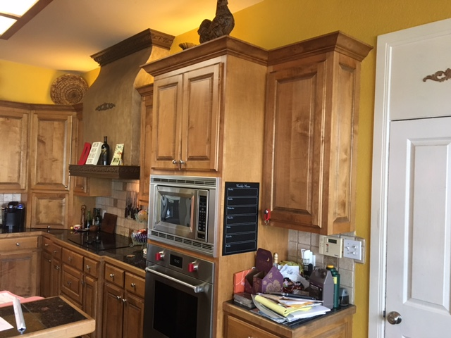 Before: Dark stained cabinets, tumbled marble backsplash, black tile countertops
