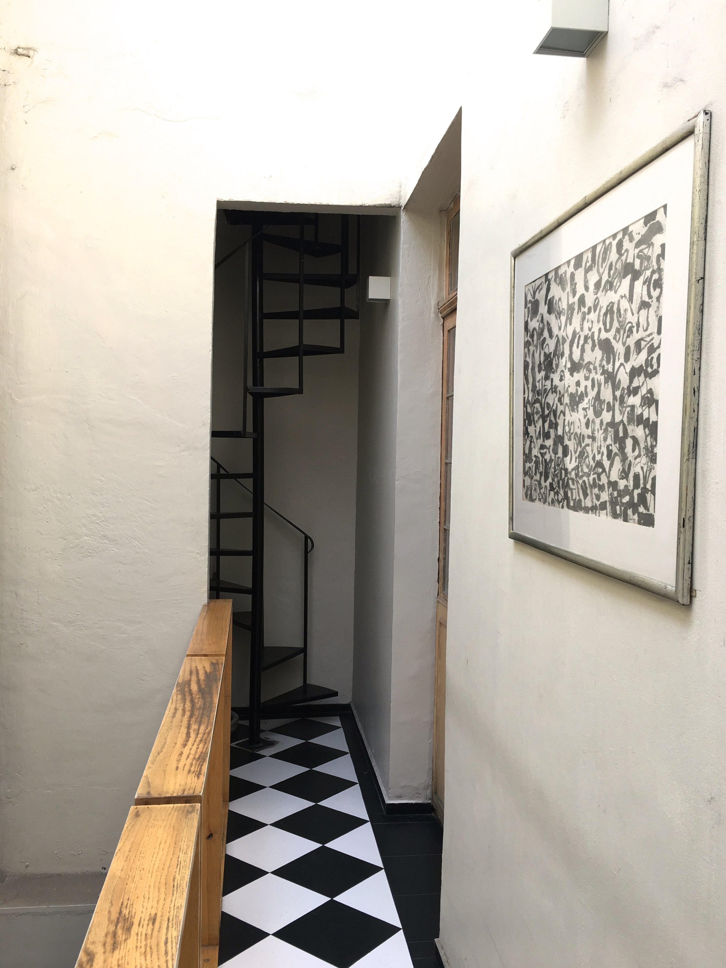 Black and white catwalk with a winding staircase leading to the balcony.