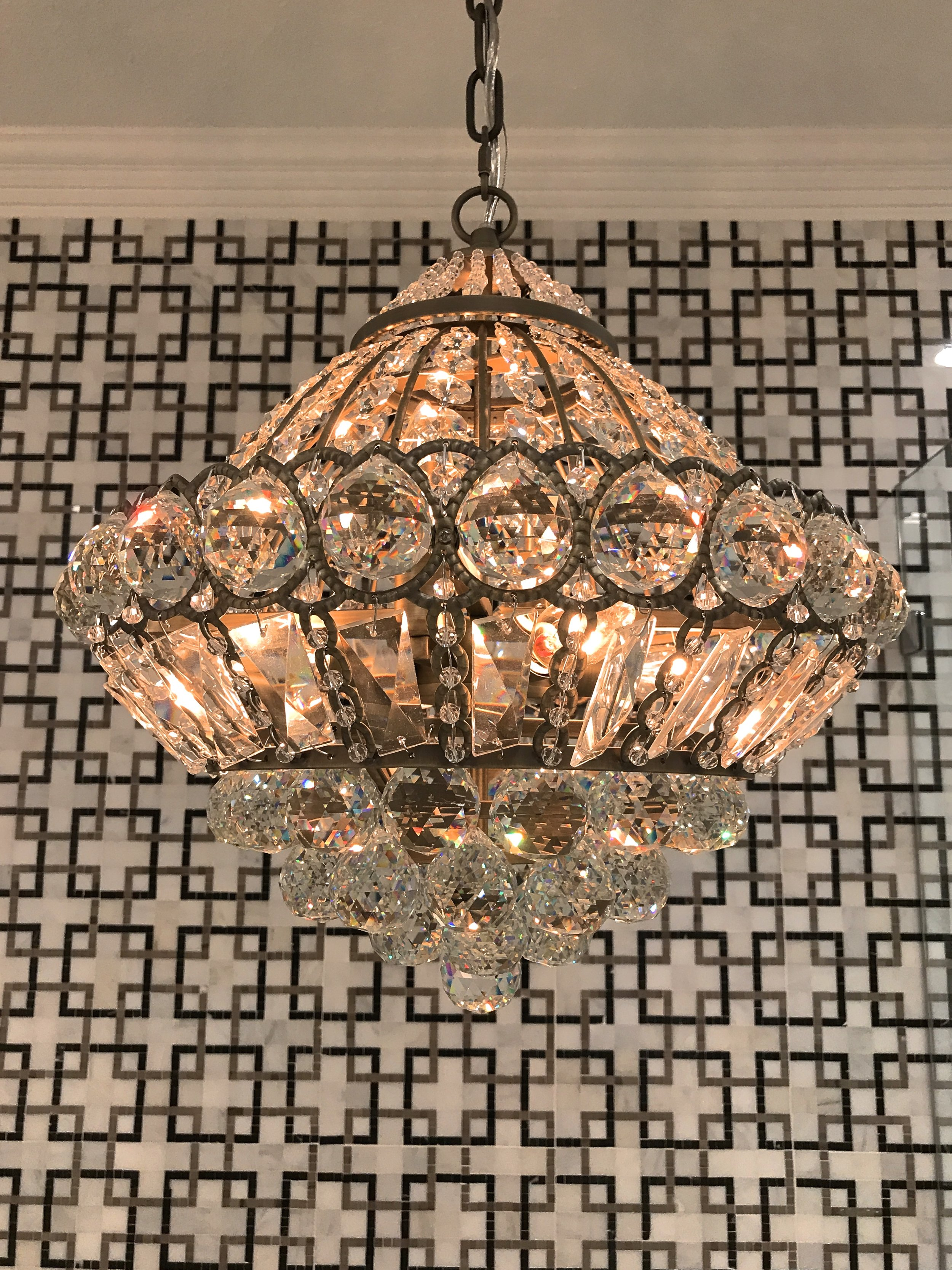 Crystal and brass chandelier over the bath tub.