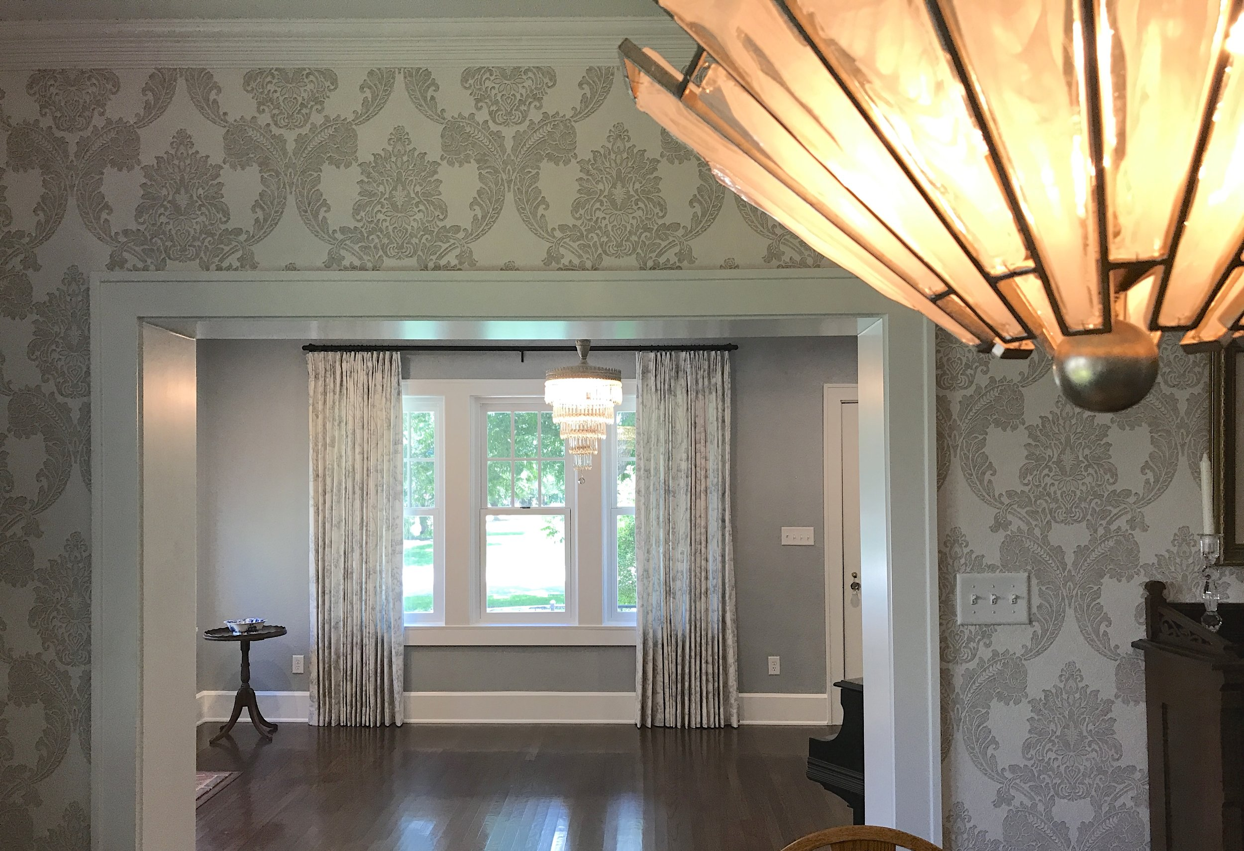 View from the dining room covered in damask wallpaper, looking into the parlor.