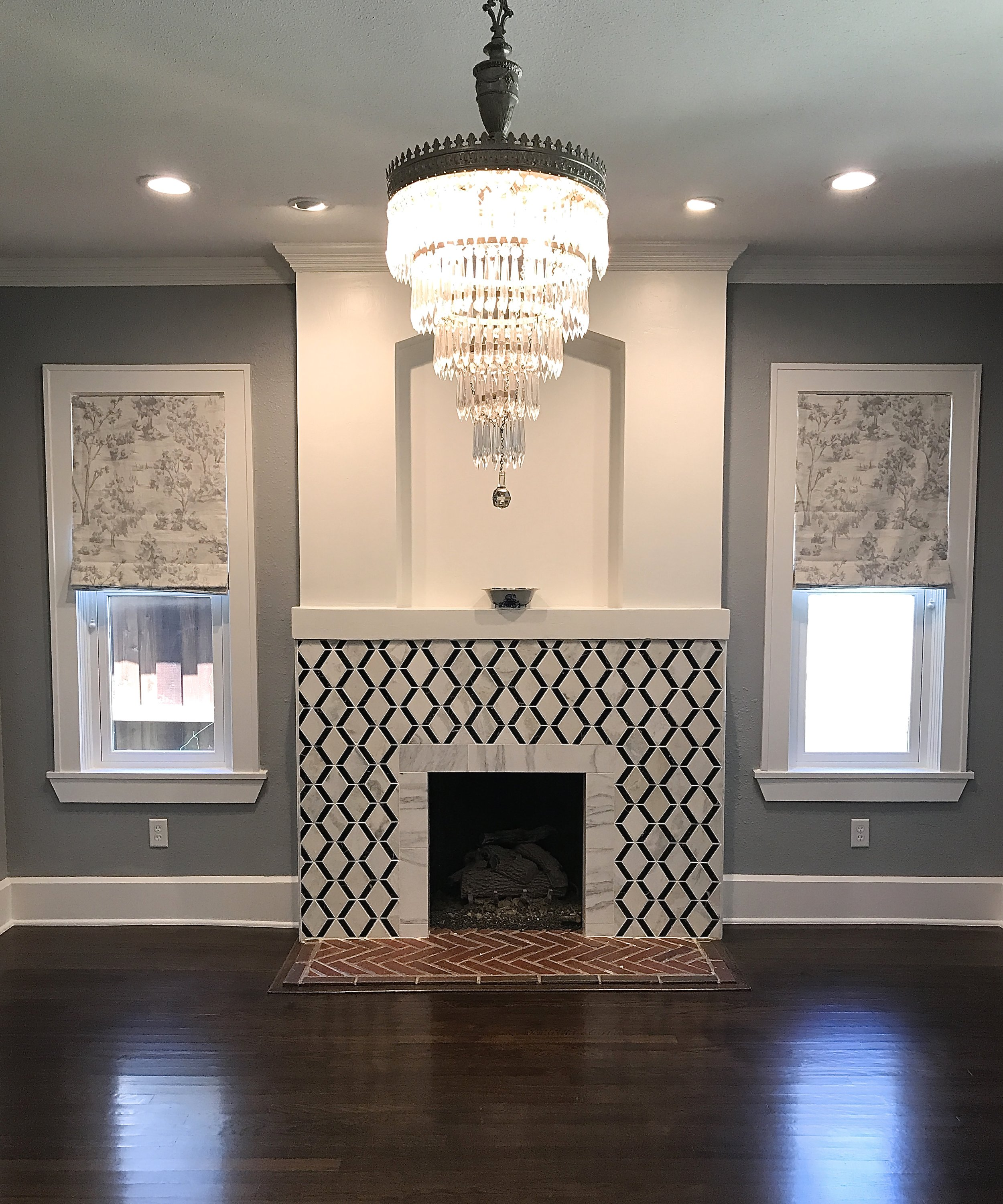 Geometric black and white wall tile surrounding the hearth