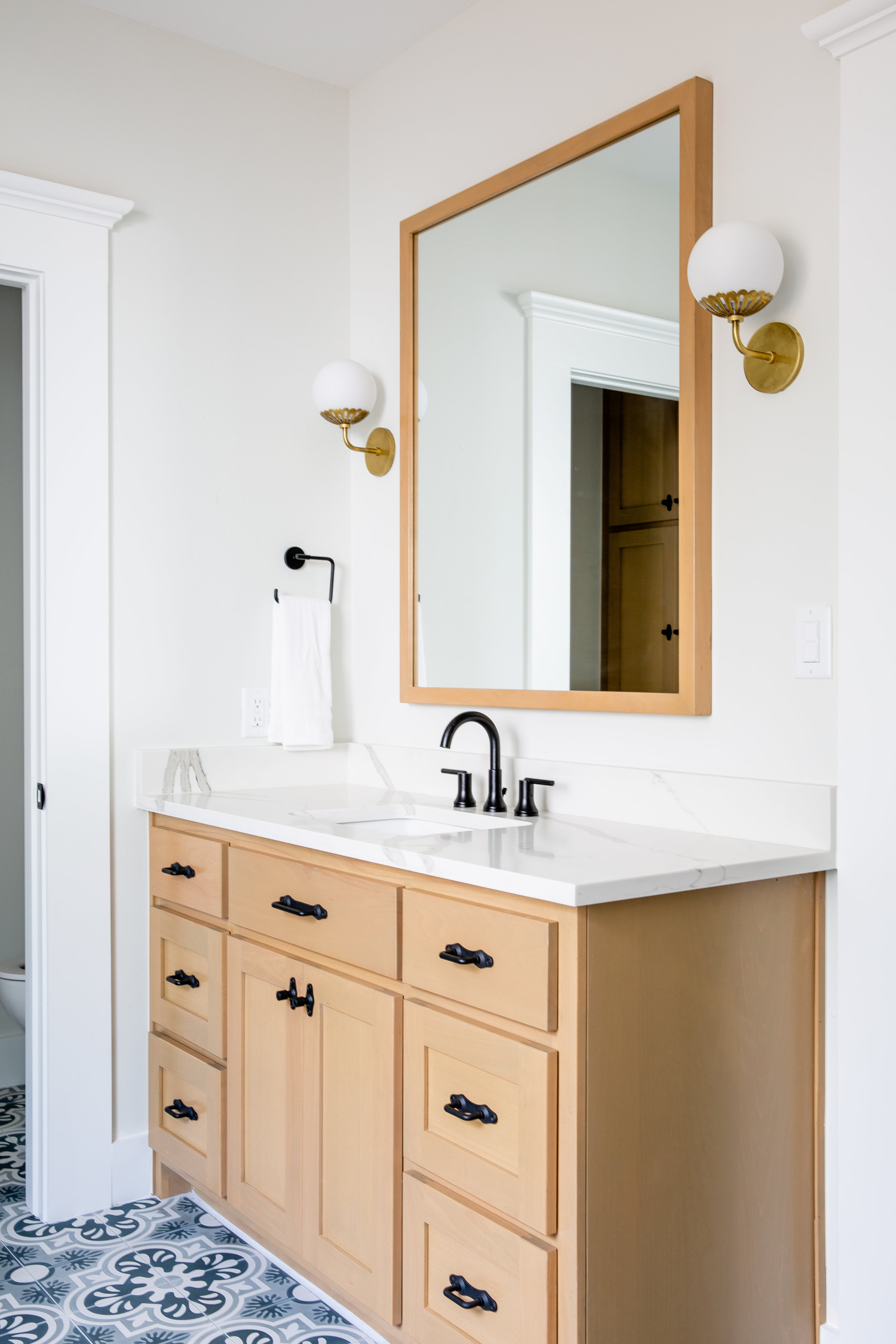 I love the rustic quality of these black plumbing fixtures by  Delta . The blonde stained cabinets provide a natural element to add visual warmth to the space. I l went for contrast with these black  Rejuvenation  cabinet pulls.