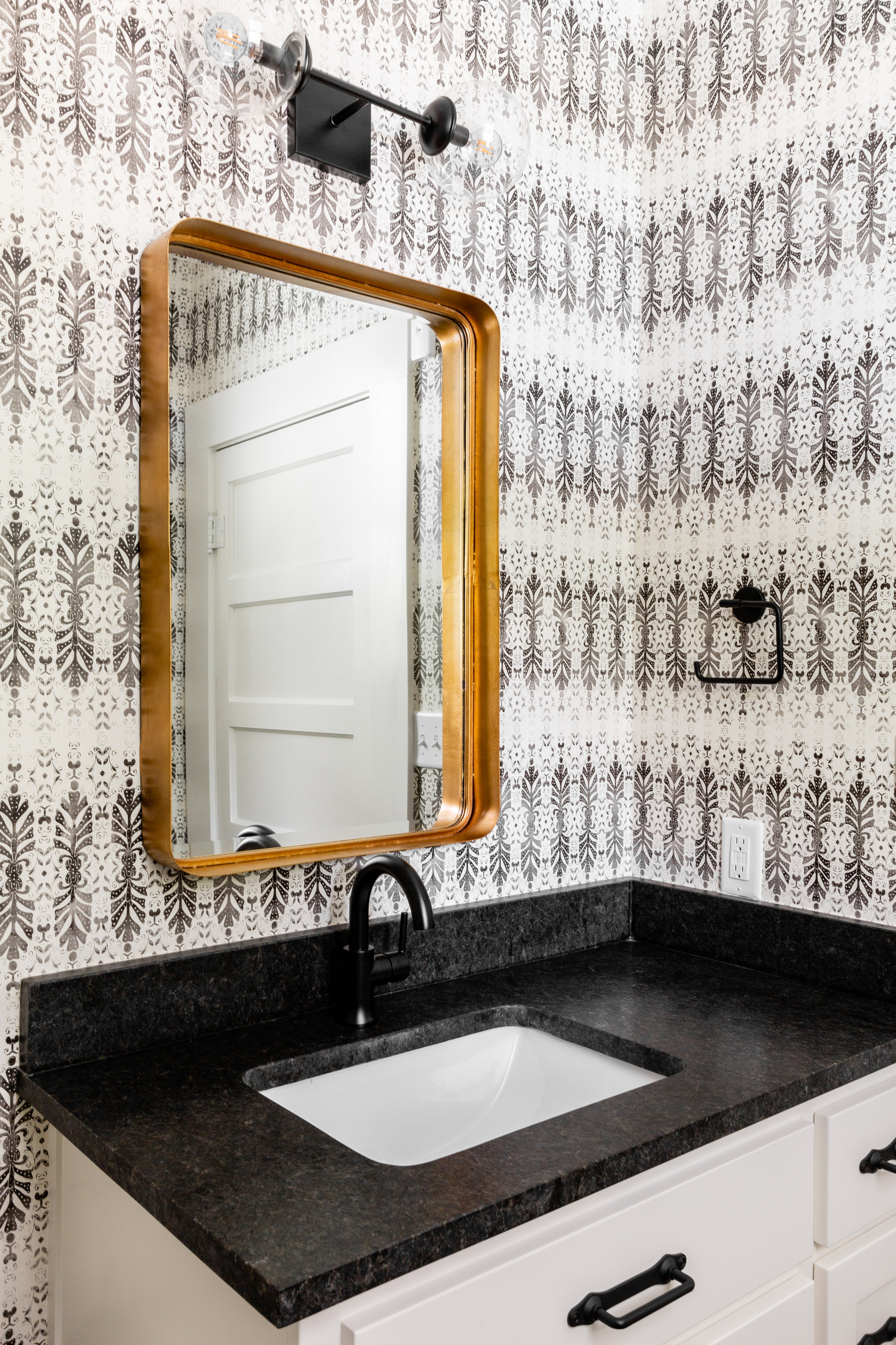 Mixed metals is something we should all embrace! I love how this brass mirror by  Uttermost  stands out against all the black & white. We went for a leathered black granite countertop for extra durability.