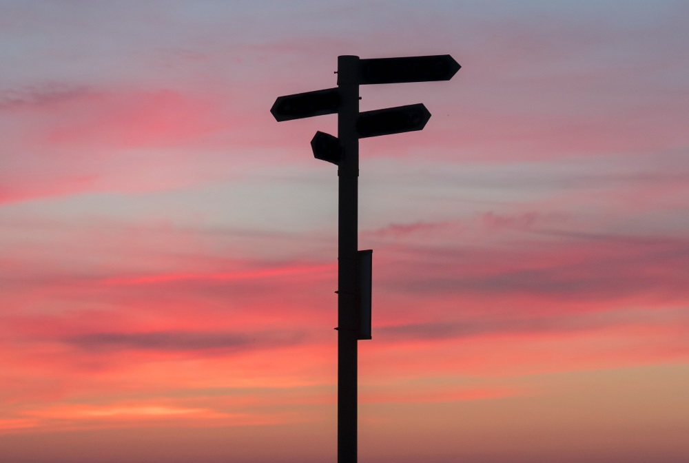 Silhouetted crossroads with several directional signs.   Source: Unsplash
