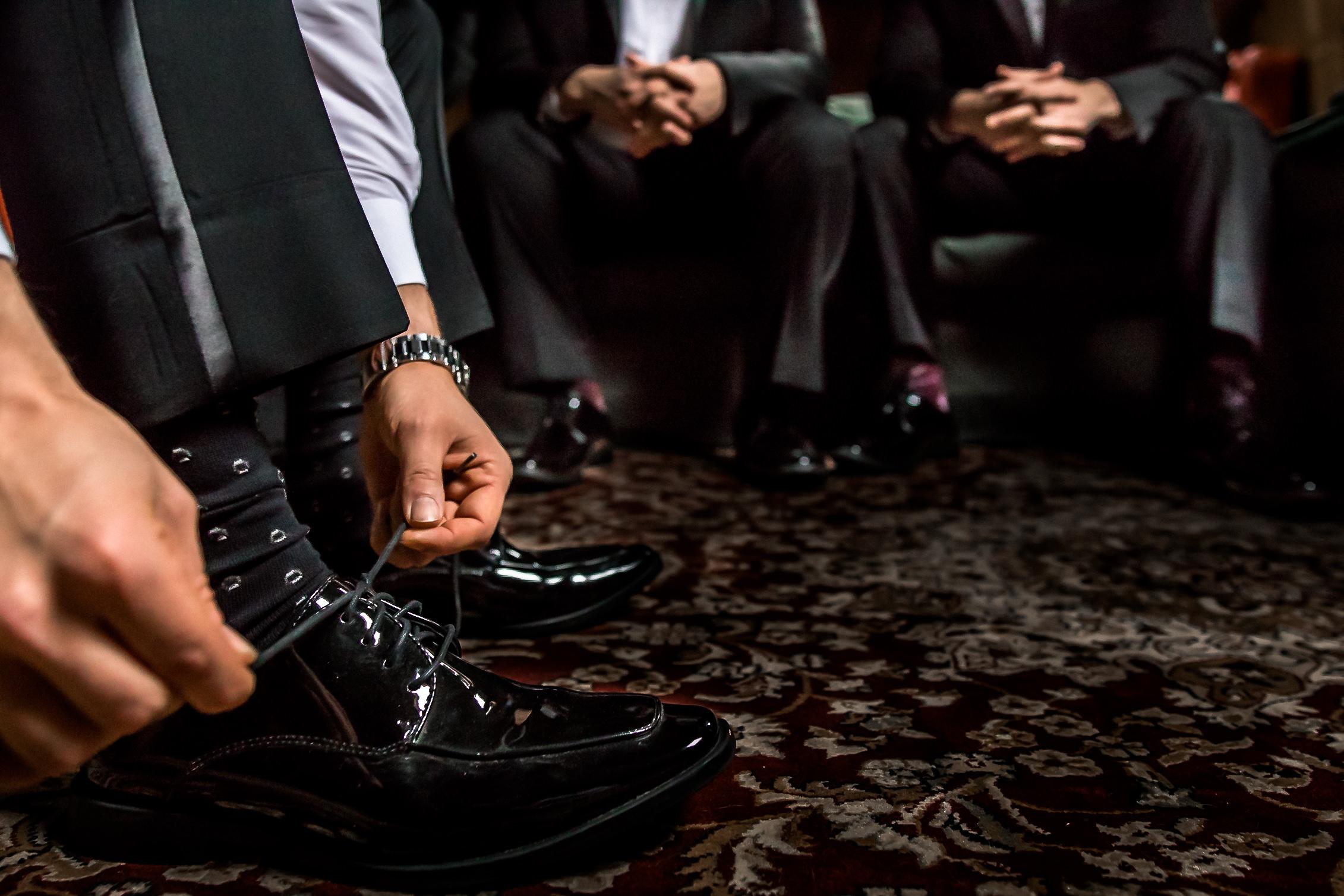 groom tying shoes groomsmen background details