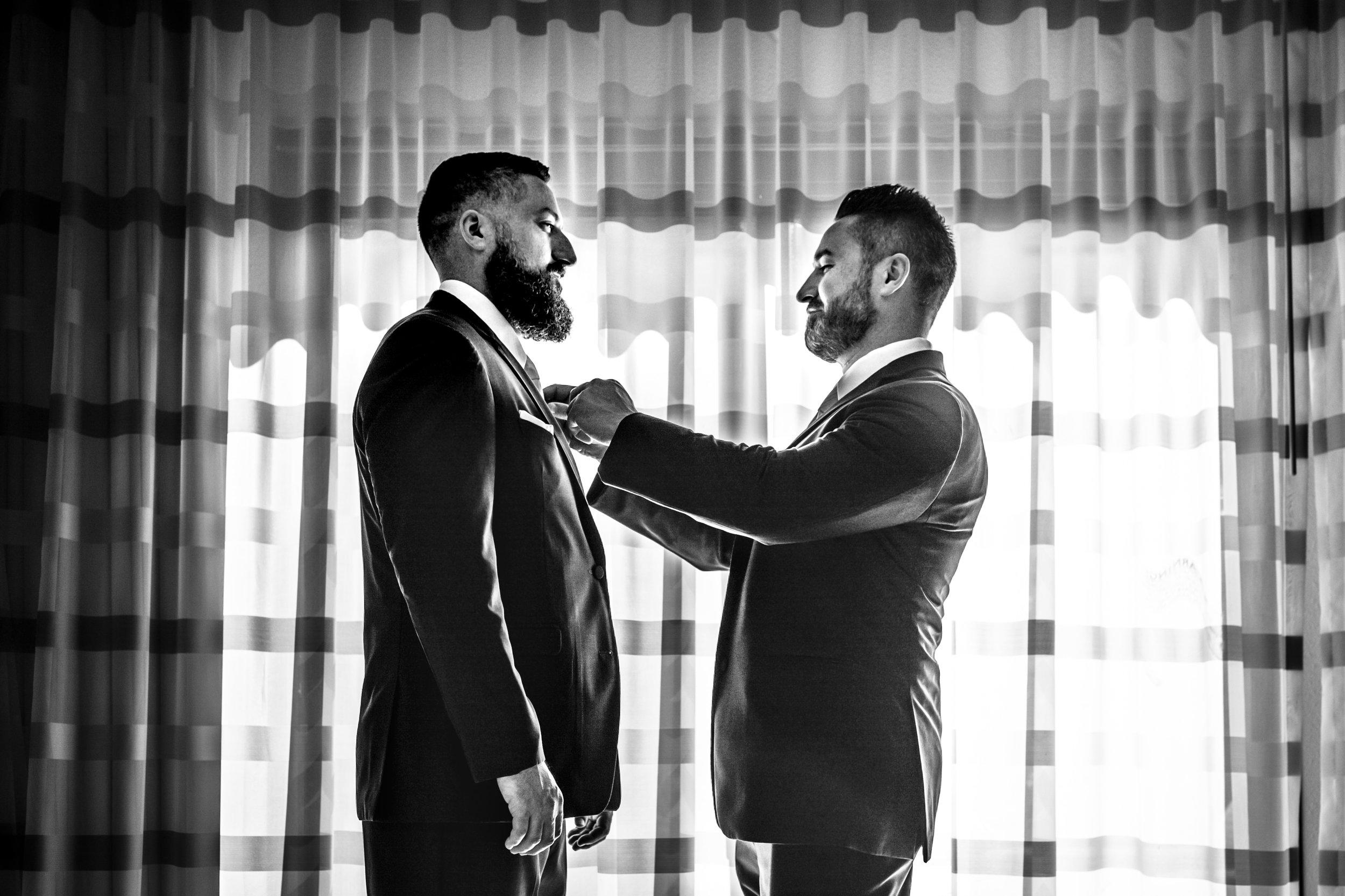 best man helping groom get dressed
