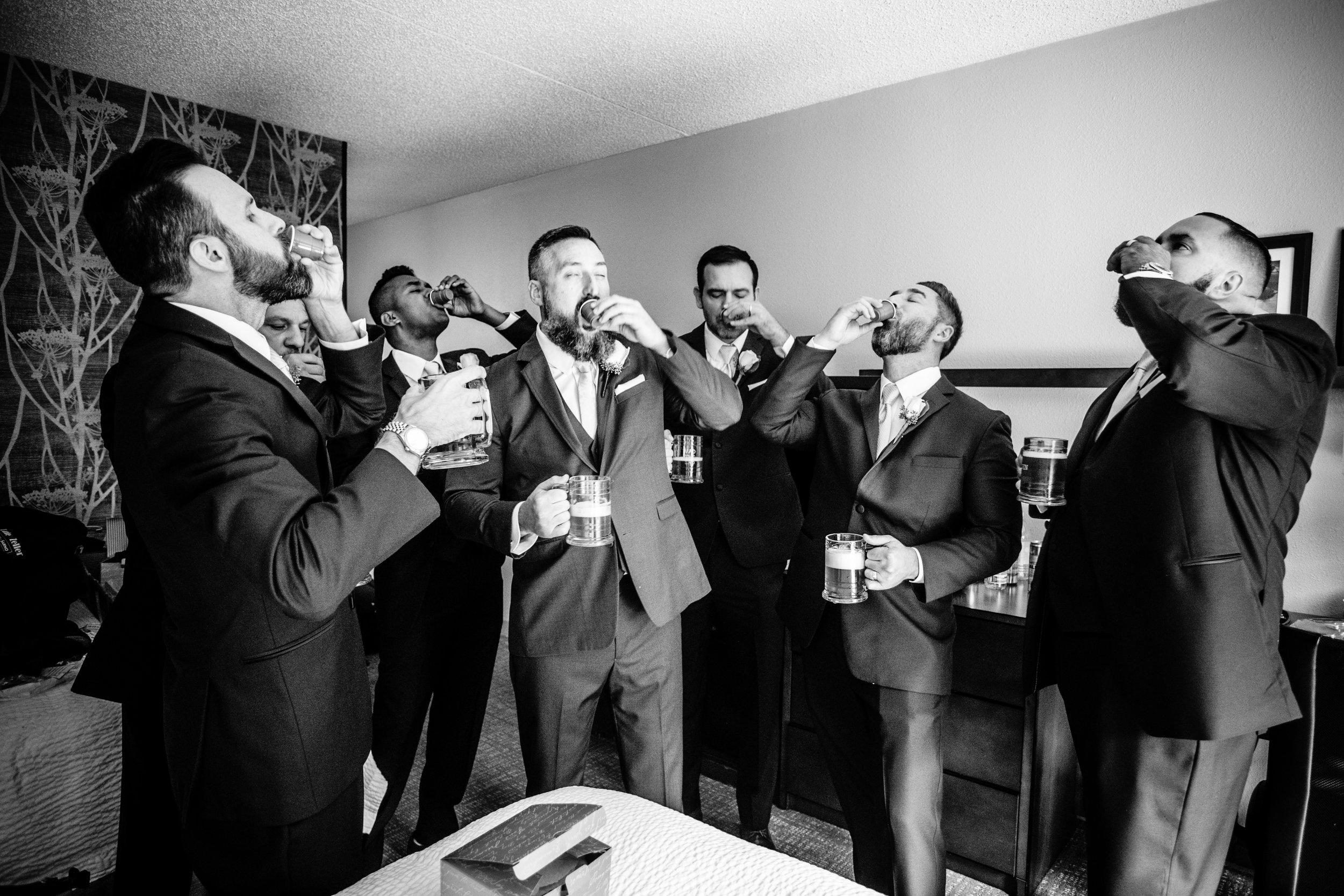 groomsmen doing shots before the weding