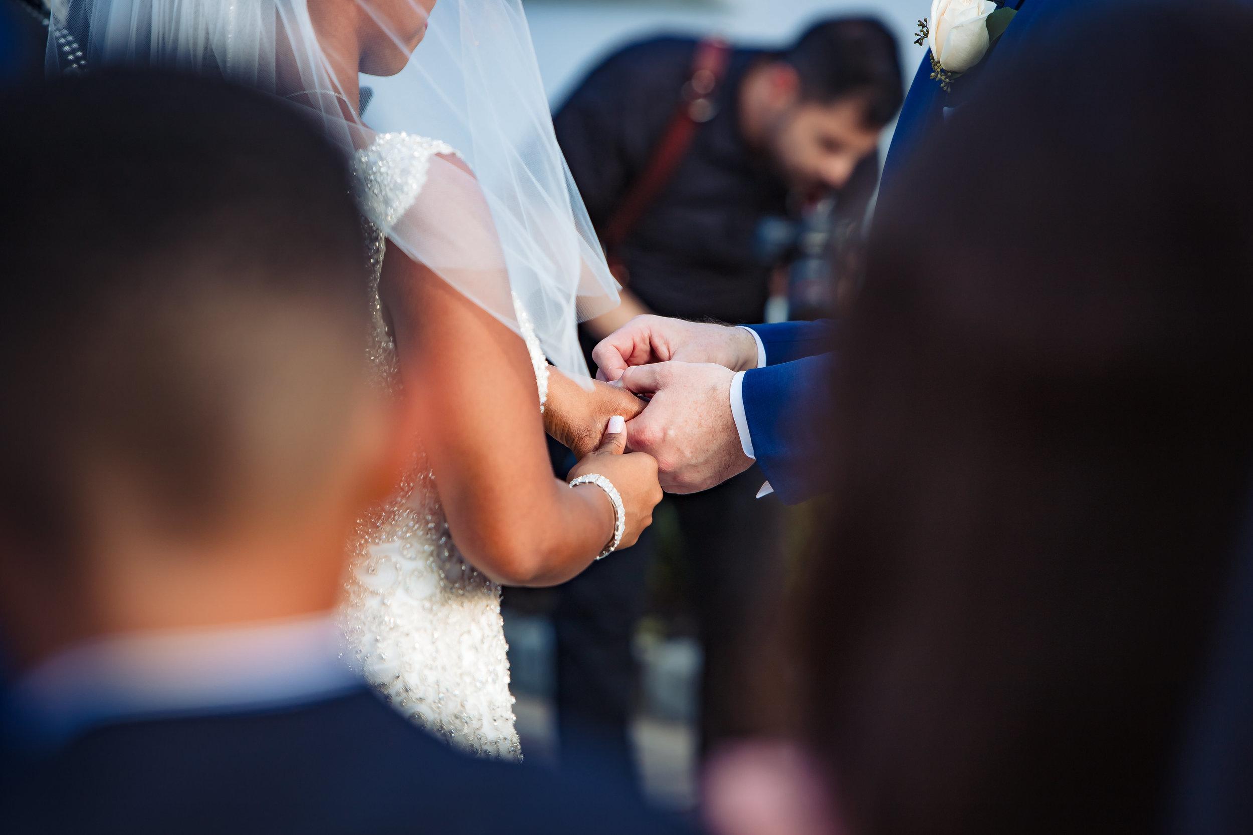 groom putting wedding ring on his bride