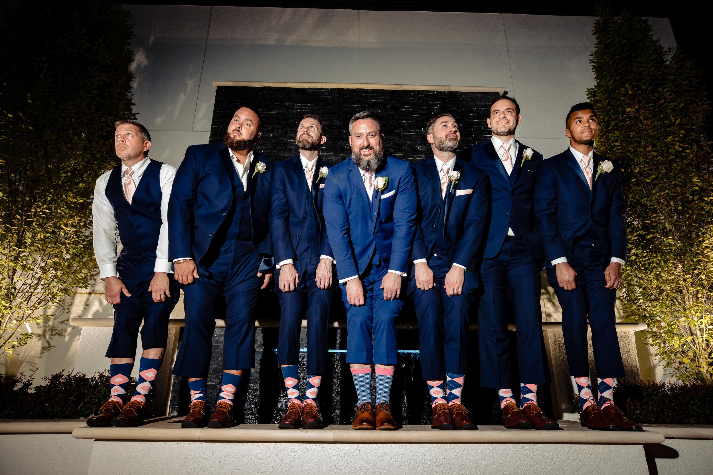 groomsmen lifting their pant legs to show their matching socks