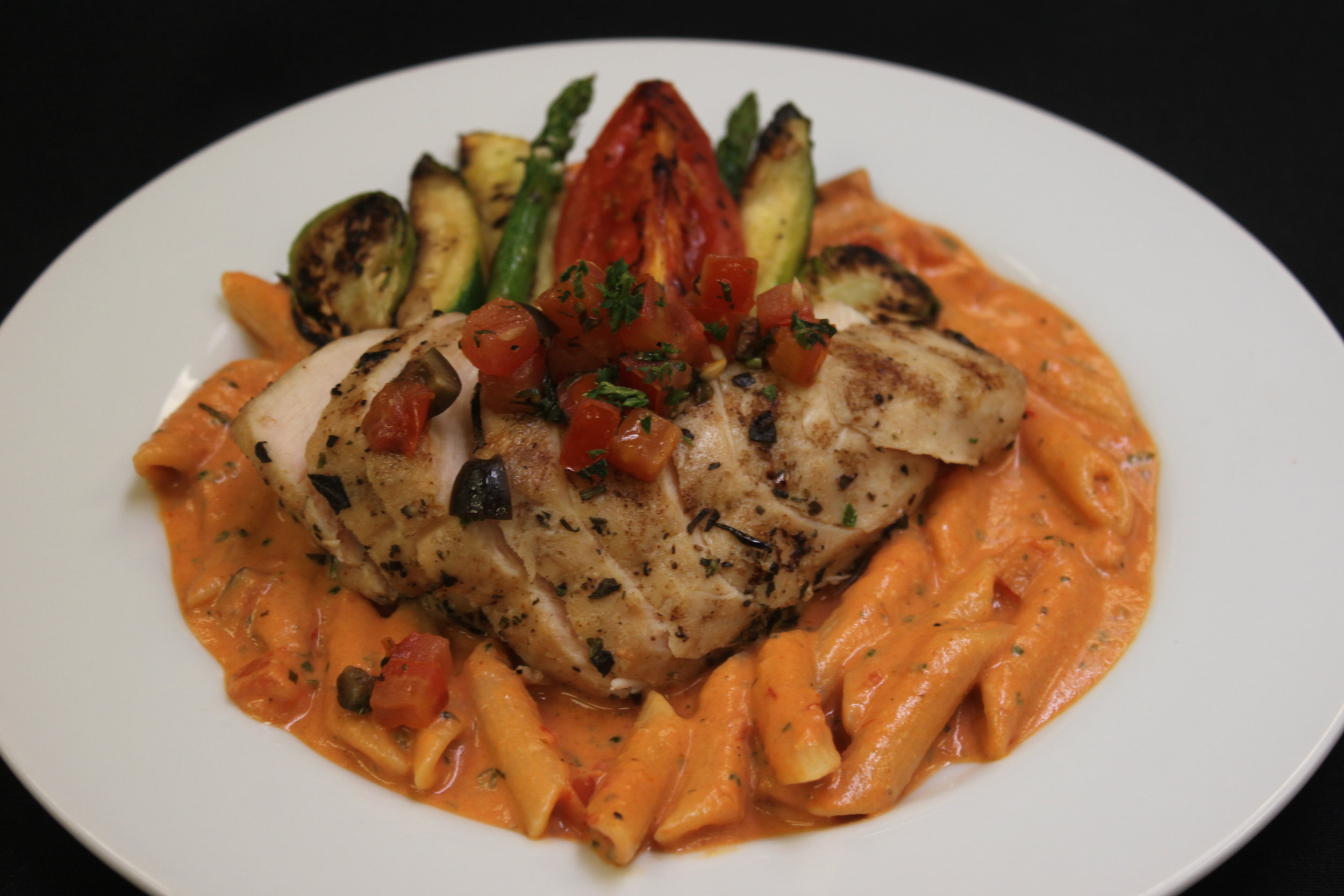 Penne Mozzarella Pasta Topped with Grilled Mediterranean Herb Chicken Breast, and Grilled Vegetable Medley