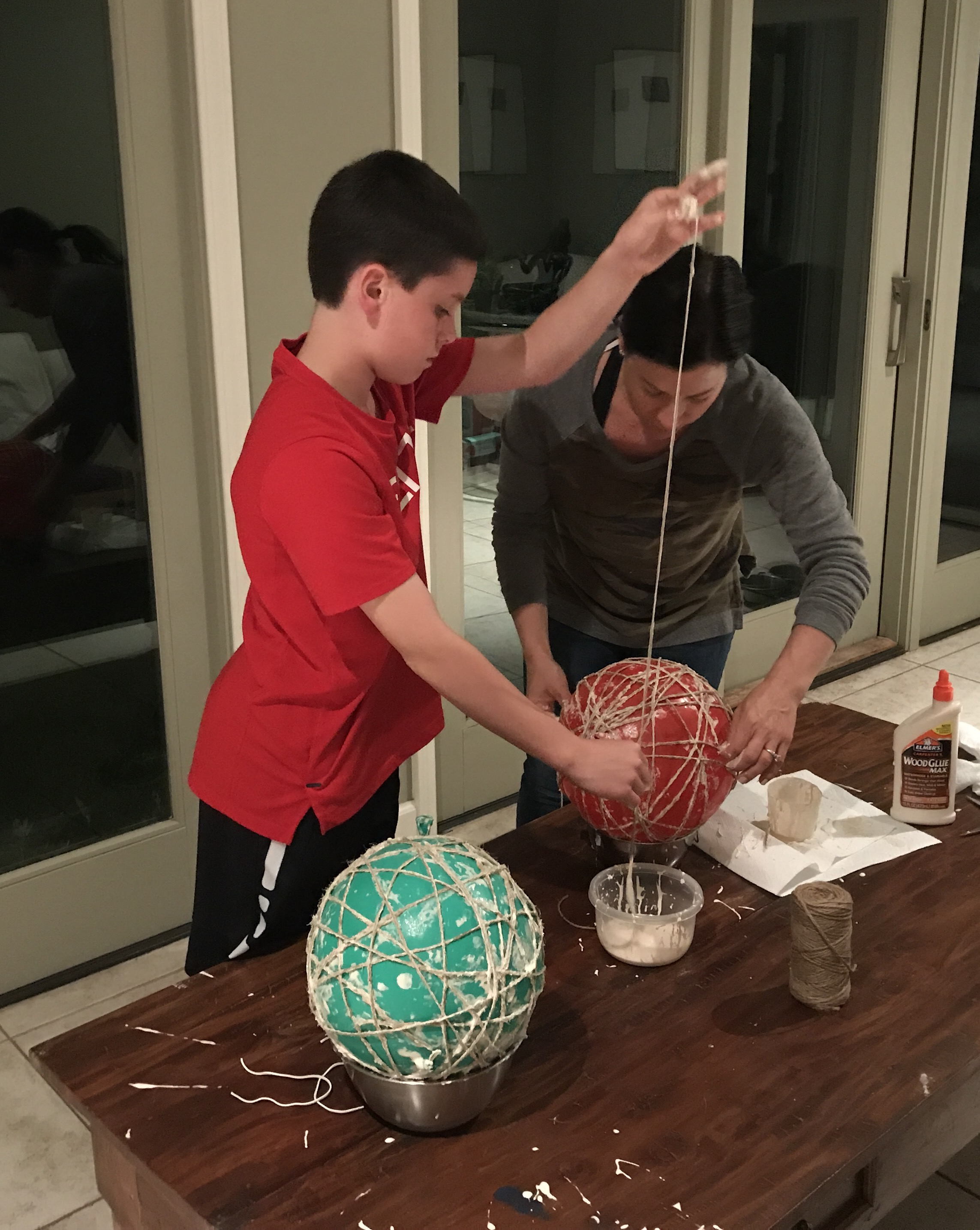 Follow steps below:   Wrap the ball with twine dipped in glue (you can use rubber gloves here). I like to cut the twine into 4' pieces because it's easier to wrap around the balloon without getting tangled.