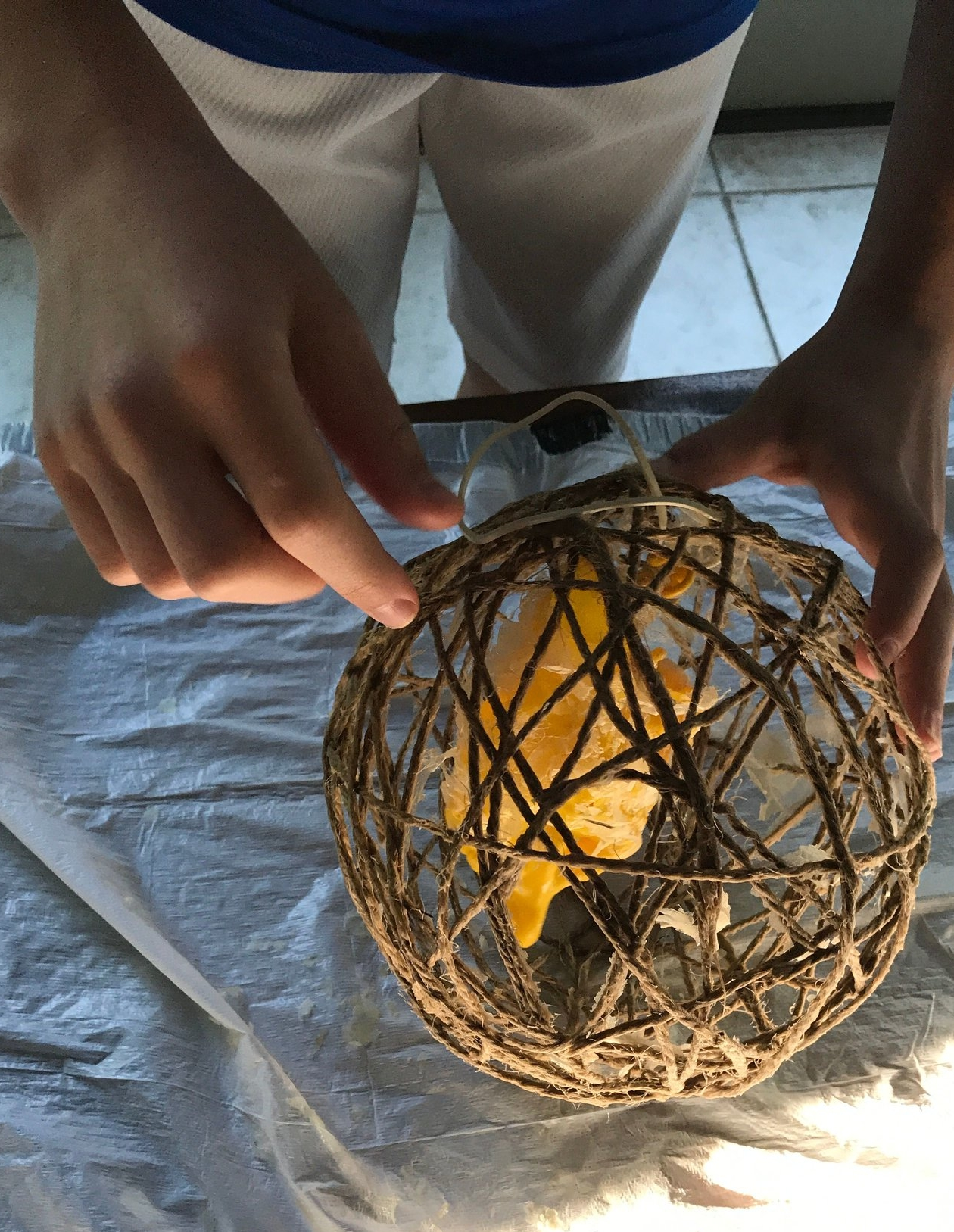 Pop the balloon inside the ball with a scissors.Remove the dried glue that is not attached to the twine. This part is definitely messy, it's a good idea to have newspaper or a trash bag under the ball.