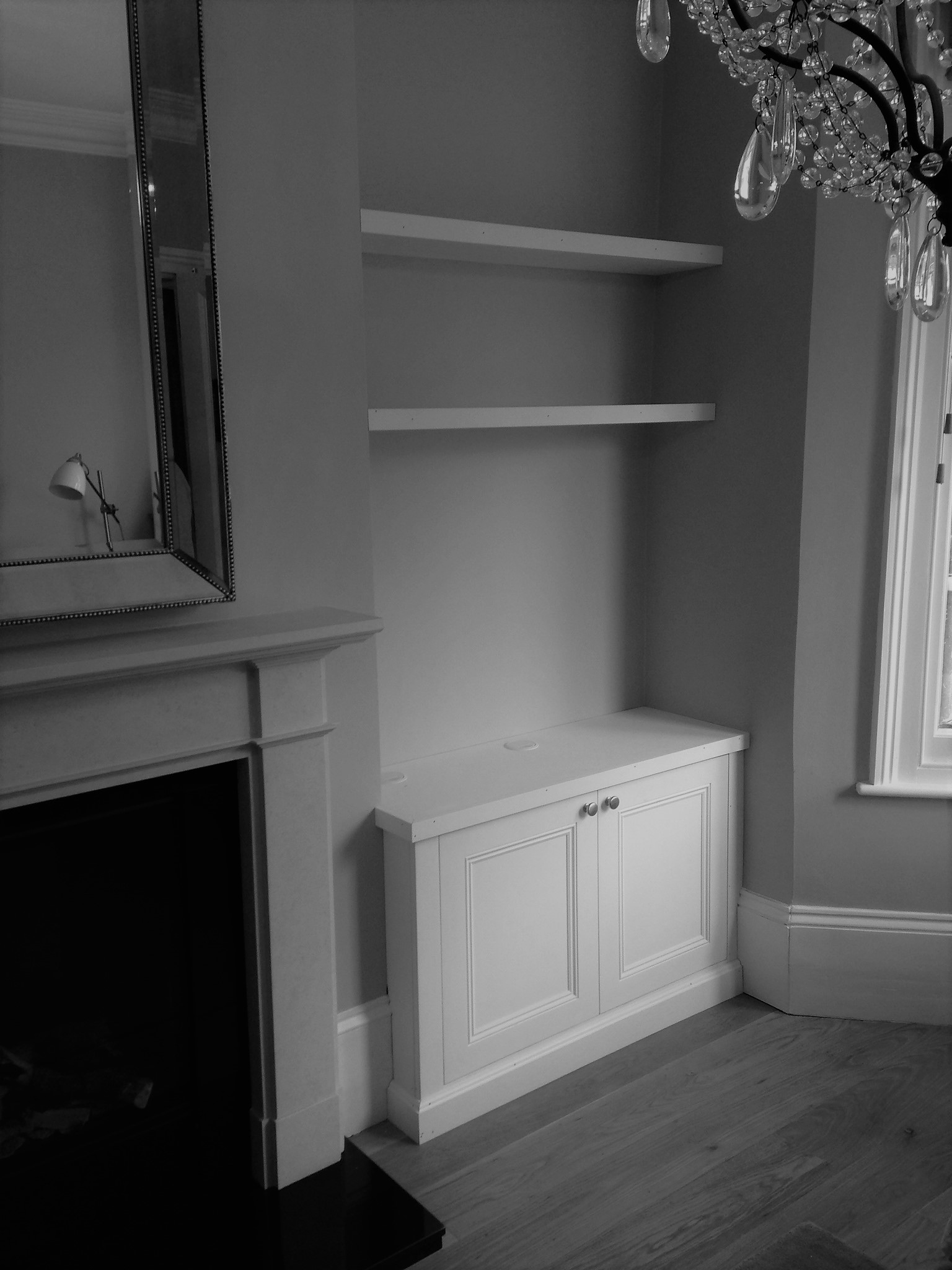 A classic alcove unit with a pair of fitted floating shelves above.