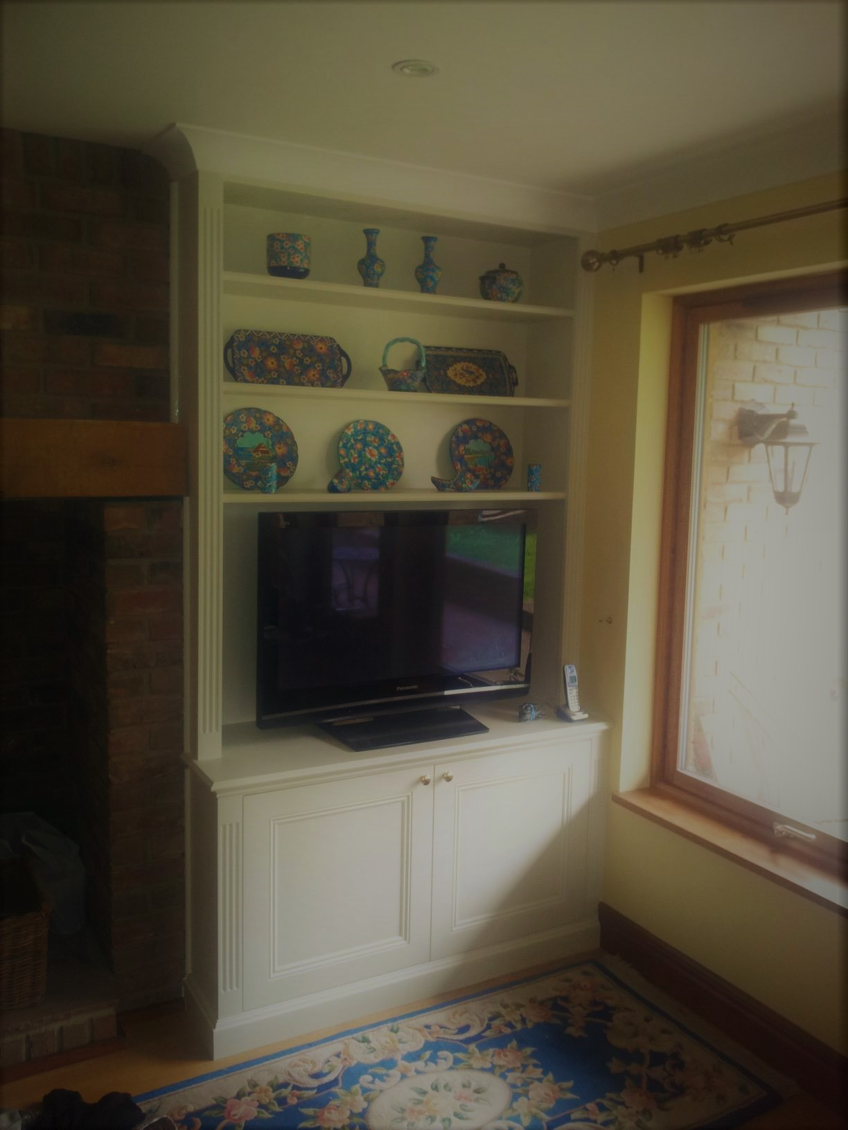 A classic alcove unit, utilizing the top box space with a free standing television and ornaments above.