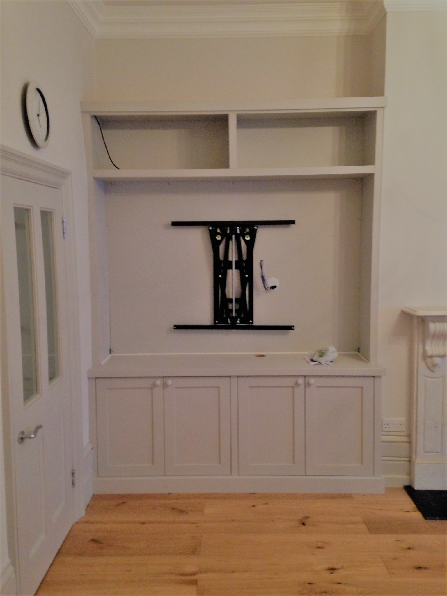 This bespoke cabinet shows how the cabling for a television can be hidden by using wire holes in the top box vertically above the wire hole in the bottom cabinet.
