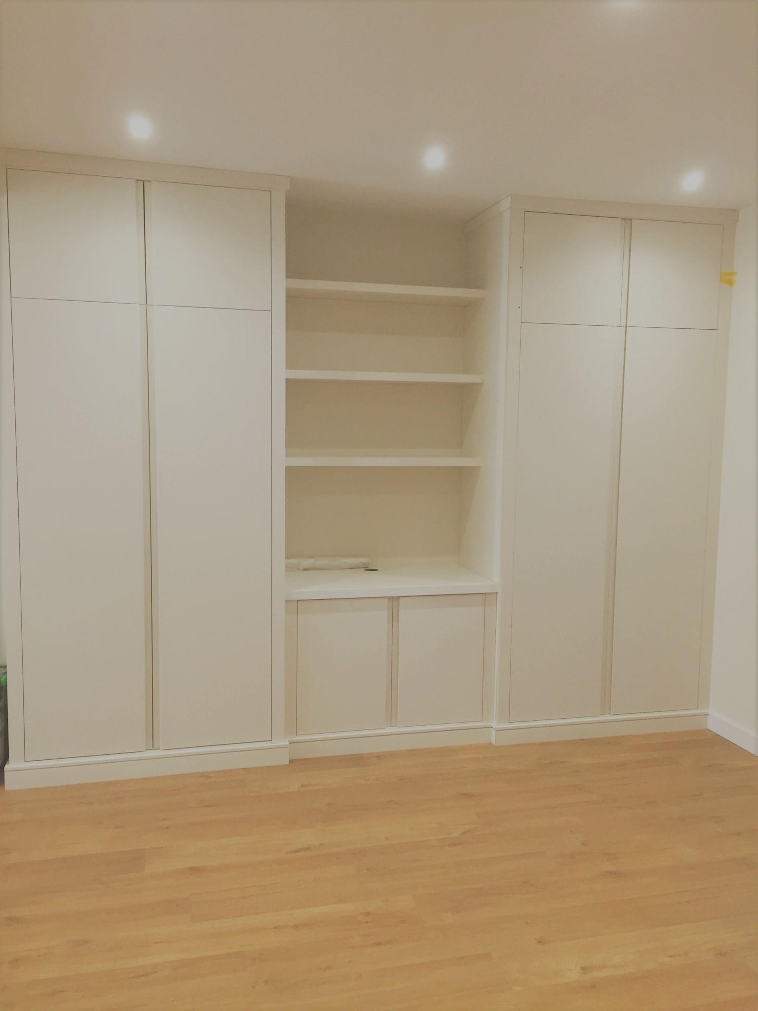A contemporary wardrobe with a dividing base unit and shelves.