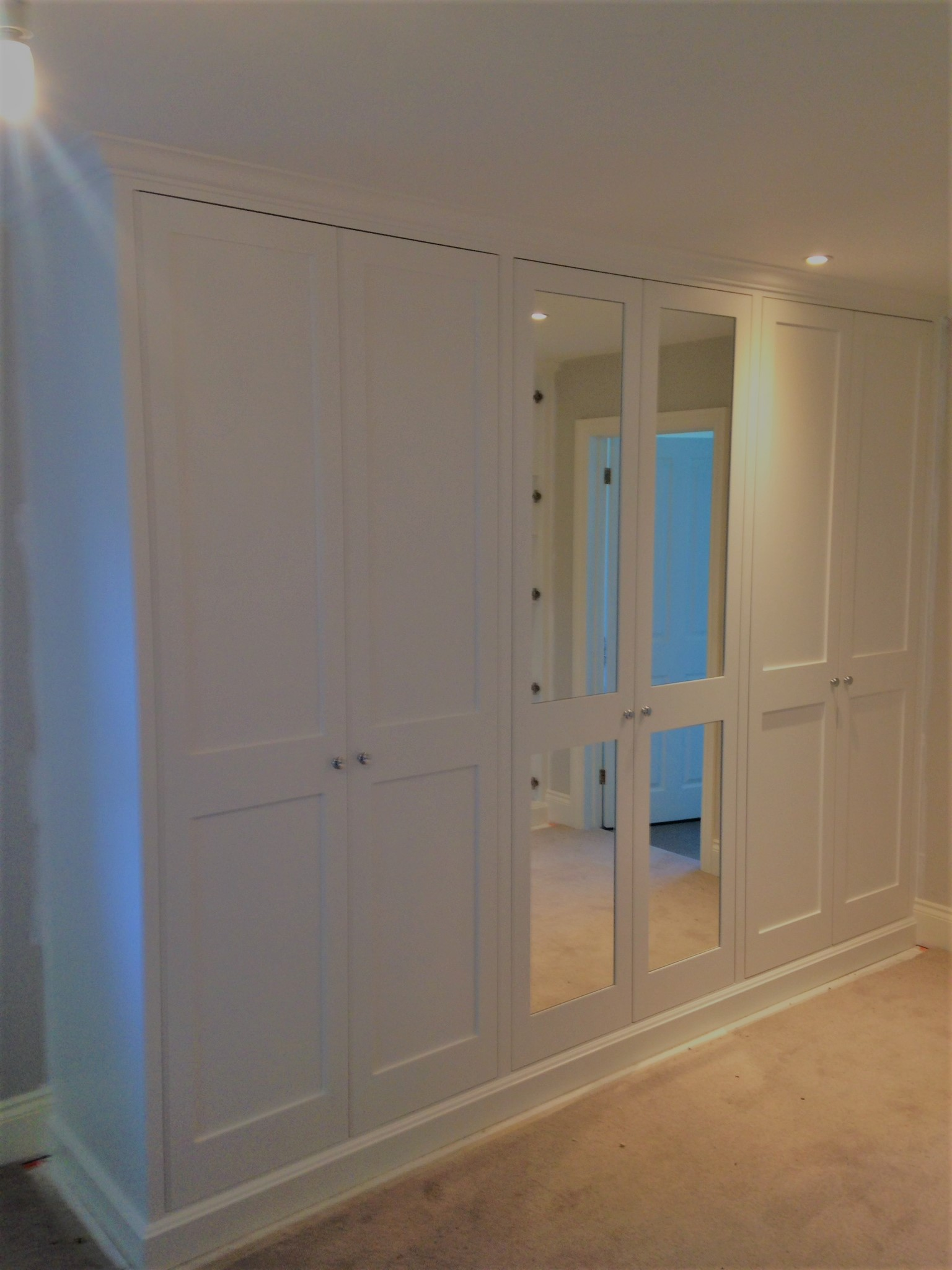 A 6 door wardrobe with a central pair of mirrored panel doors.