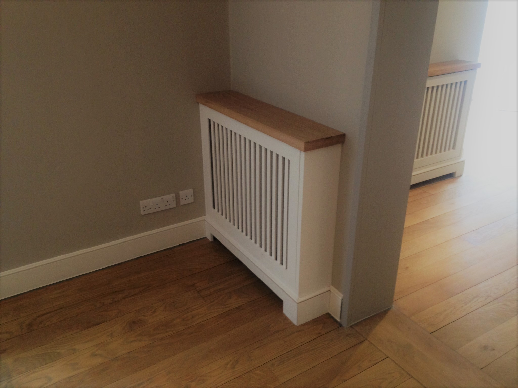 A modern radiator cover adds a certain something to a room, for photographs or ornaments to be placed upon.