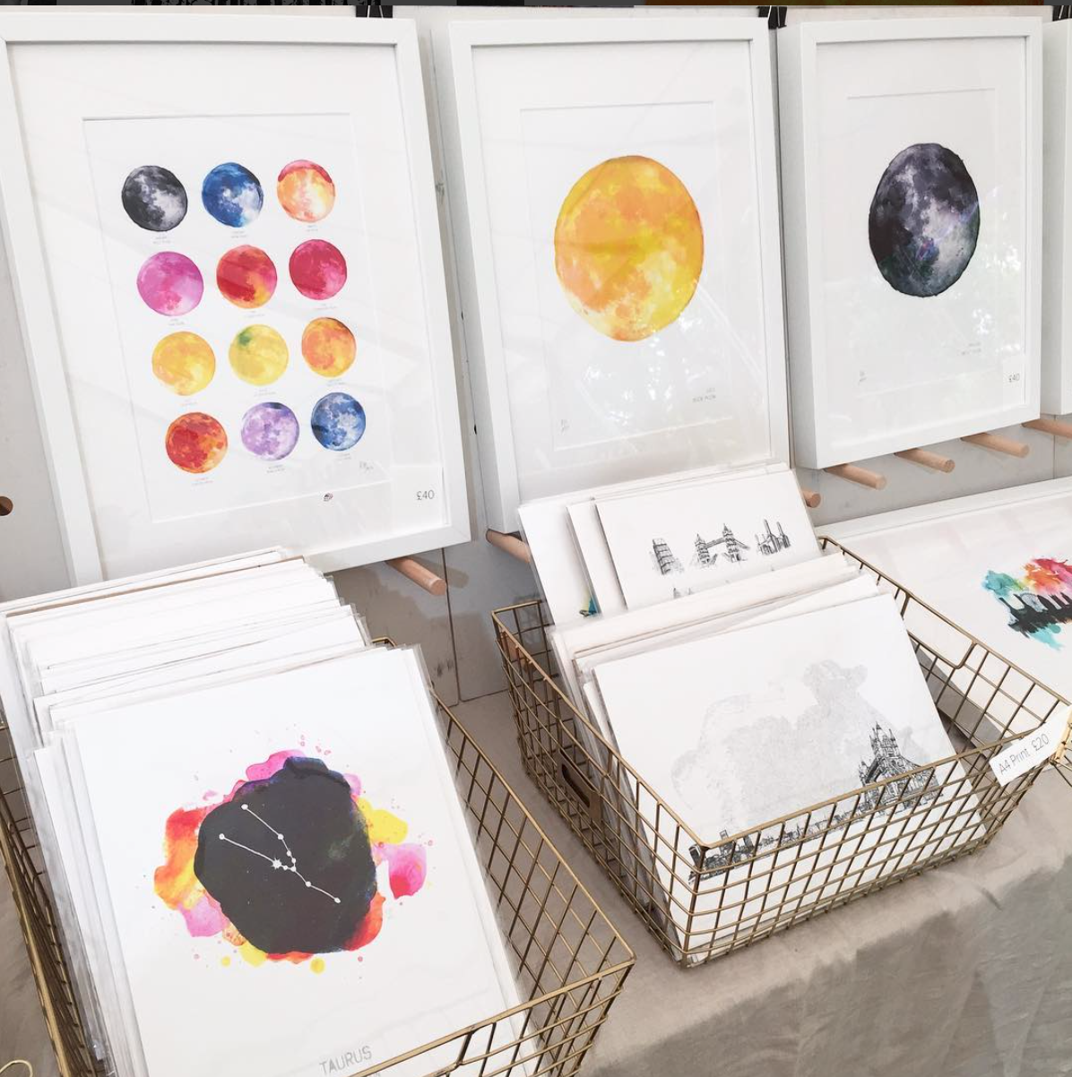 art prints by drawn together art collective display at a craft fair stall