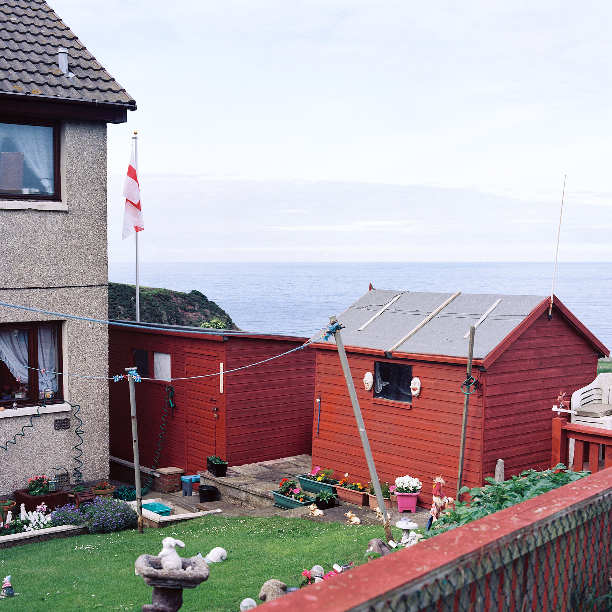 A St. George's cross is raised above a garden close to the north sea coast in Burnmouth, Scotland
