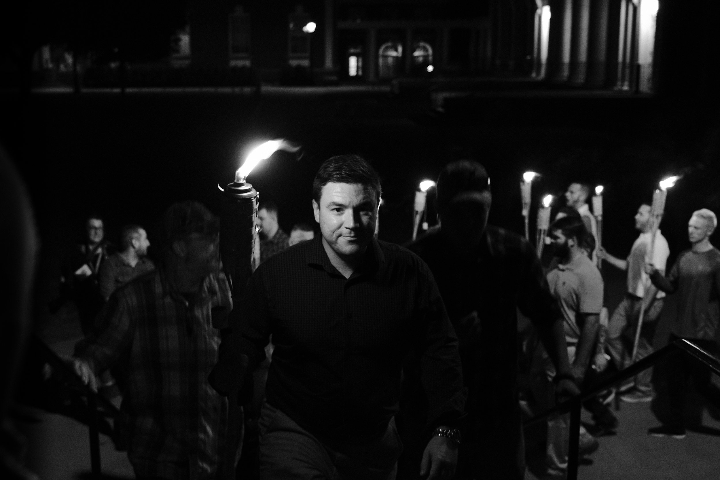 Jason Kessler (above) led the congregation as they moved haphazardly through the UVA campus. He was surrounded by a security detail and a handful of notable white supremacist celebrities including Richard Spencer, Evan McLaren, and Christopher Cantwell.