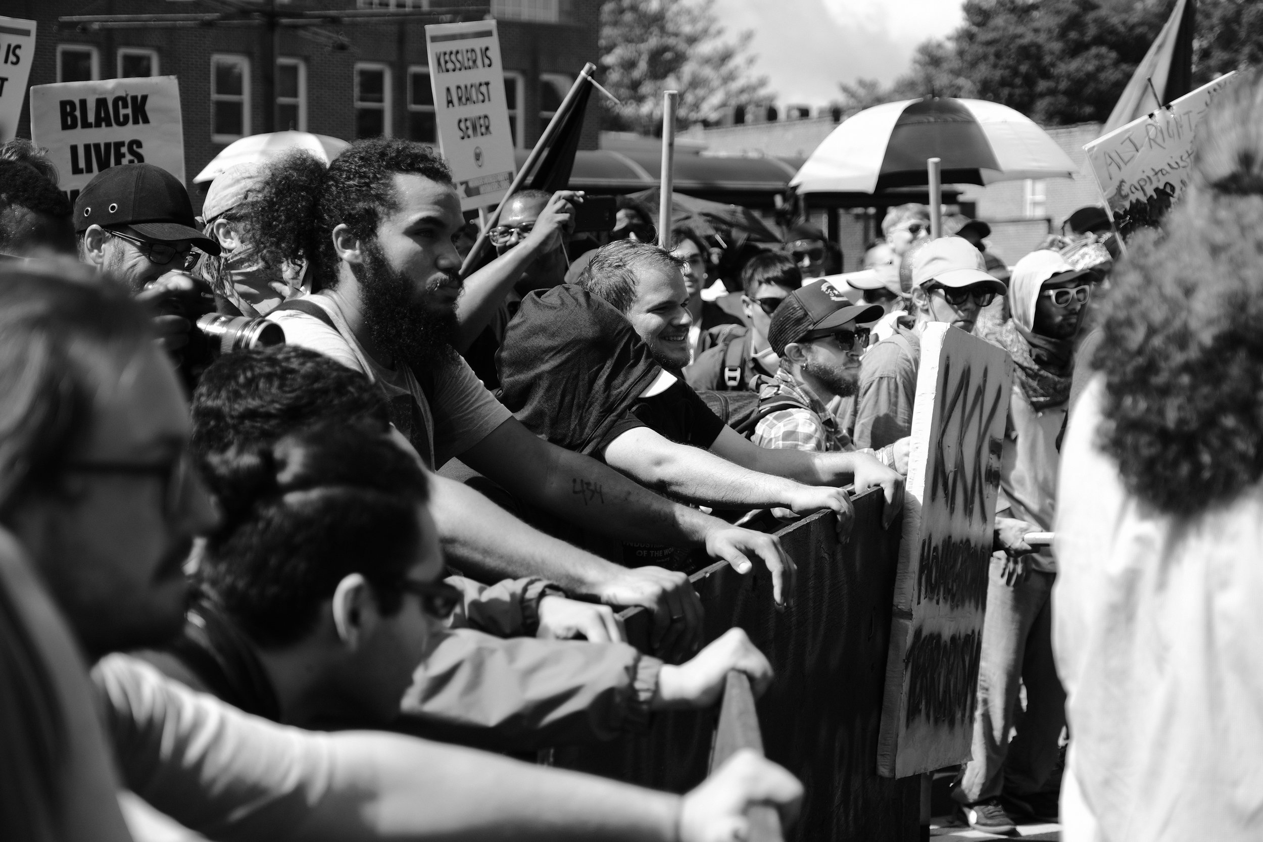 Throughout the morning, small conflicts erupted in the street in front of Emancipation Park. Protesters held hard banners in groups to defend against thrown projectiles and white supremacists who started pushing out of the permitted area and into the street. The Unite the Right attendees preferred personal shields advertizing their affiliations which are often considered prized possessions.
