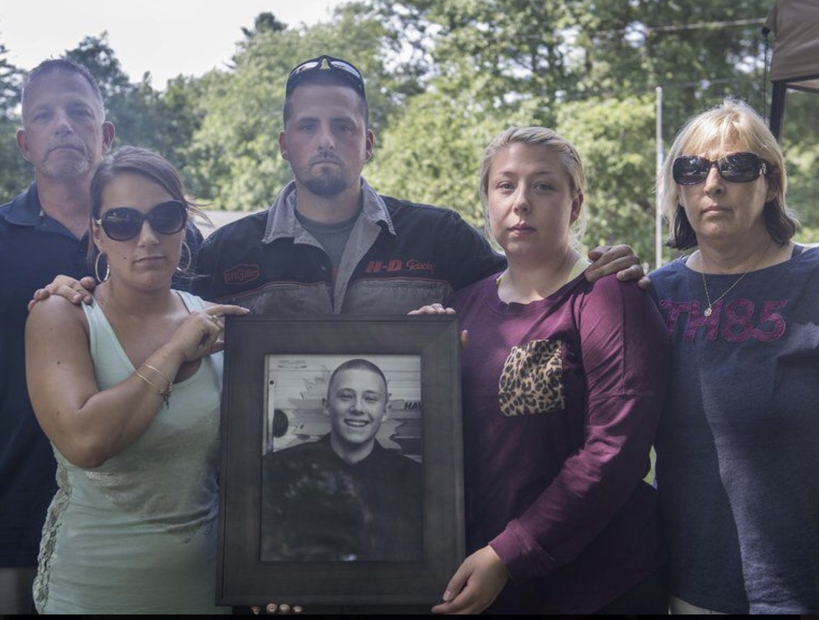 John Carter's family holds up a portrait of John. He died at age 18 from an overdose of fentanyl.  CREDIT COURTESY OF KAILYND BIGGAR