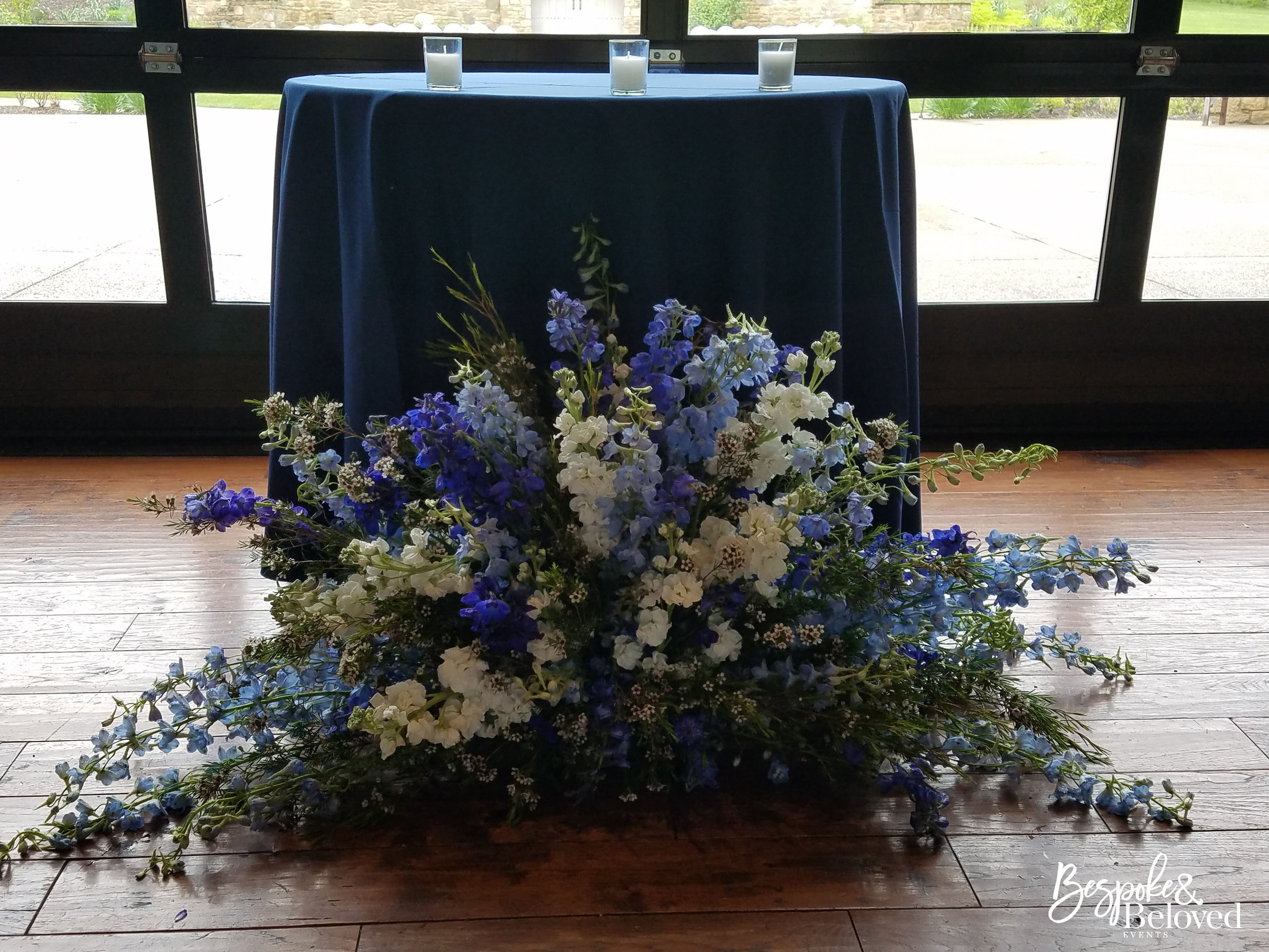 These beautiful altar flowers designed by  Sapphire and Lace Event Design  were re-purposed for the reception as decoration in front of the sweetheart table.