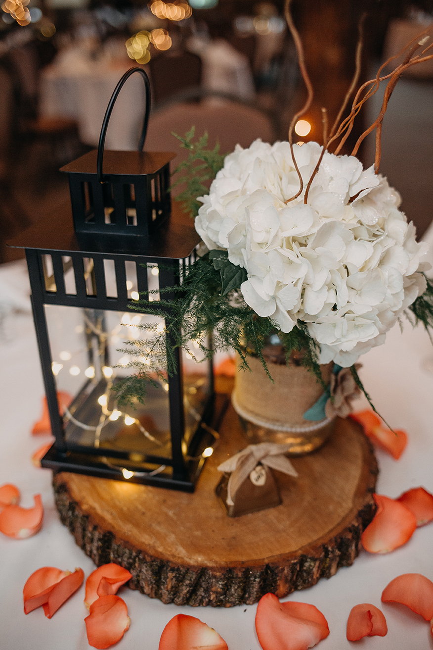 Hydrangeas, ferns, willow twigs, and rose petals from Brides and Butterflies pair perfectly with fairy lanterns and raw edge wood accents.